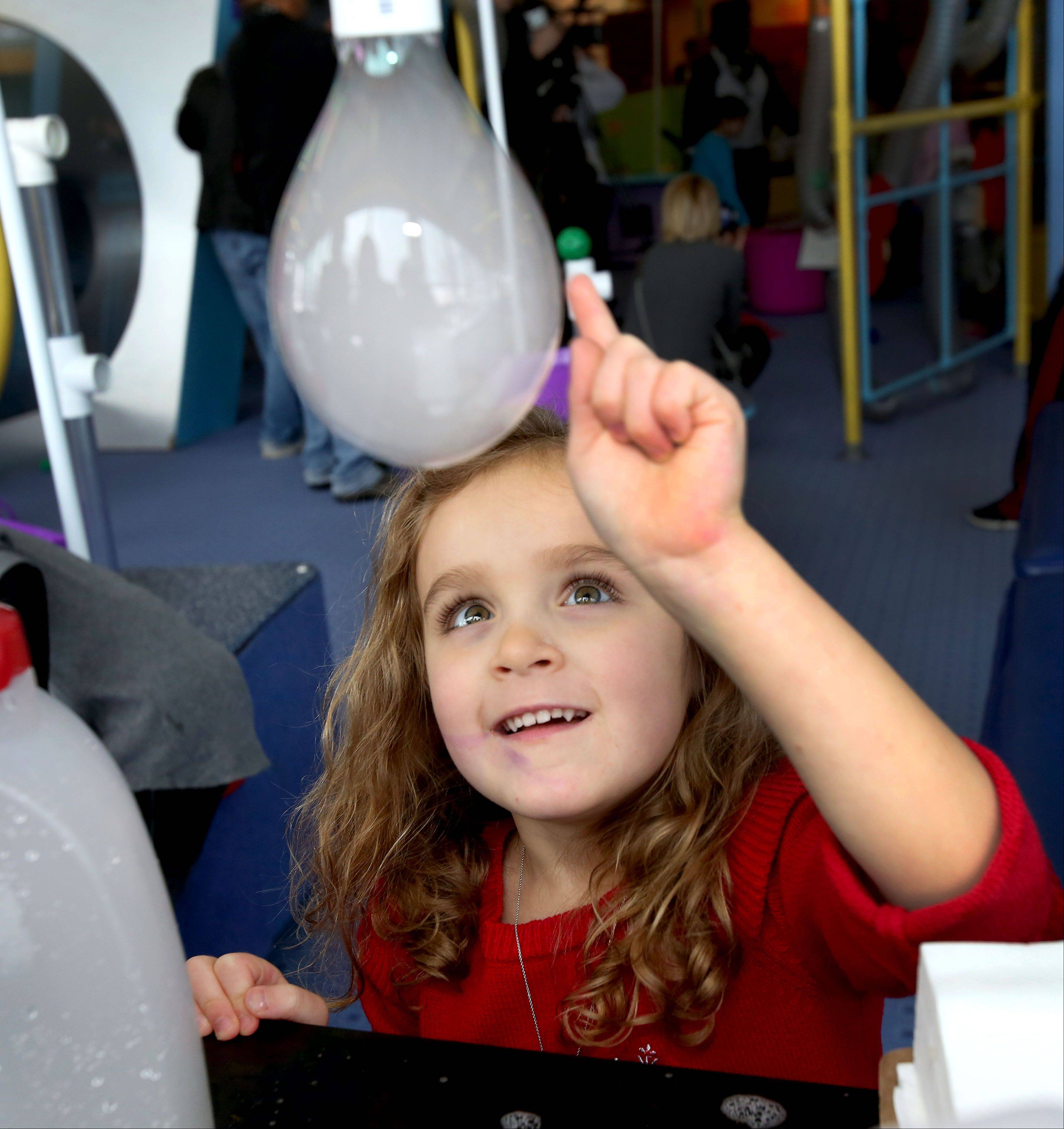 Addison Robbins, 4, of Elmhurst, gets ready to pop a dry ice bubble, just one of the activites available at the 12th annual Bubble Bash at the DuPage Children's Museum in Naperville on Tuesday.
