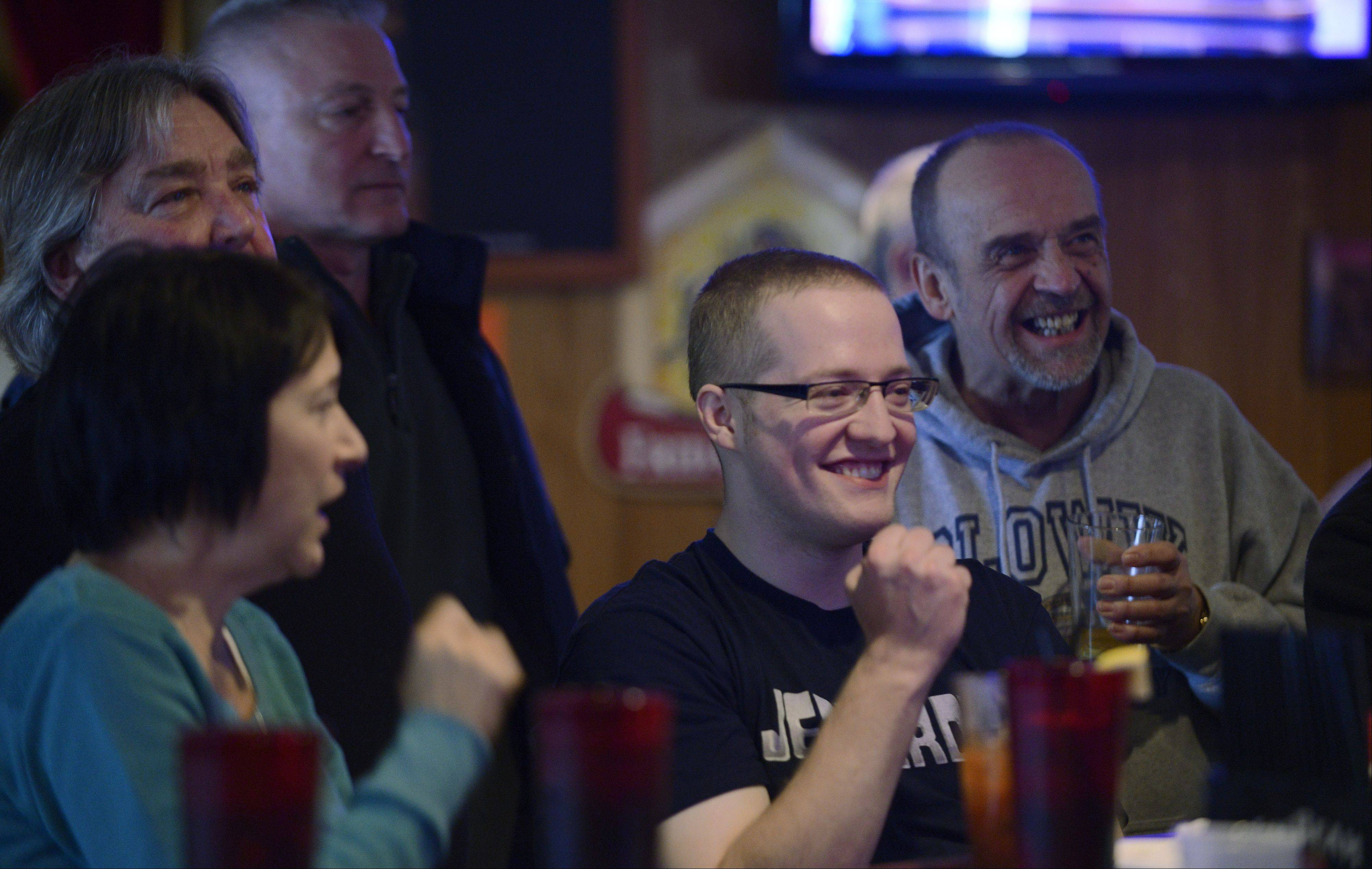 "Jerry Slowik, of Arlington Heights, gathers with family and friends to watch his latest appearance on ""Jeopardy"" at Eddie's Restaurant and Lounge in Arlington Heights on New Year's Eve Tuesday. His mom, Debbie, and dad, Jerry, stand beside him as he pumps his fist after answering a question correctly on the prerecorded program."
