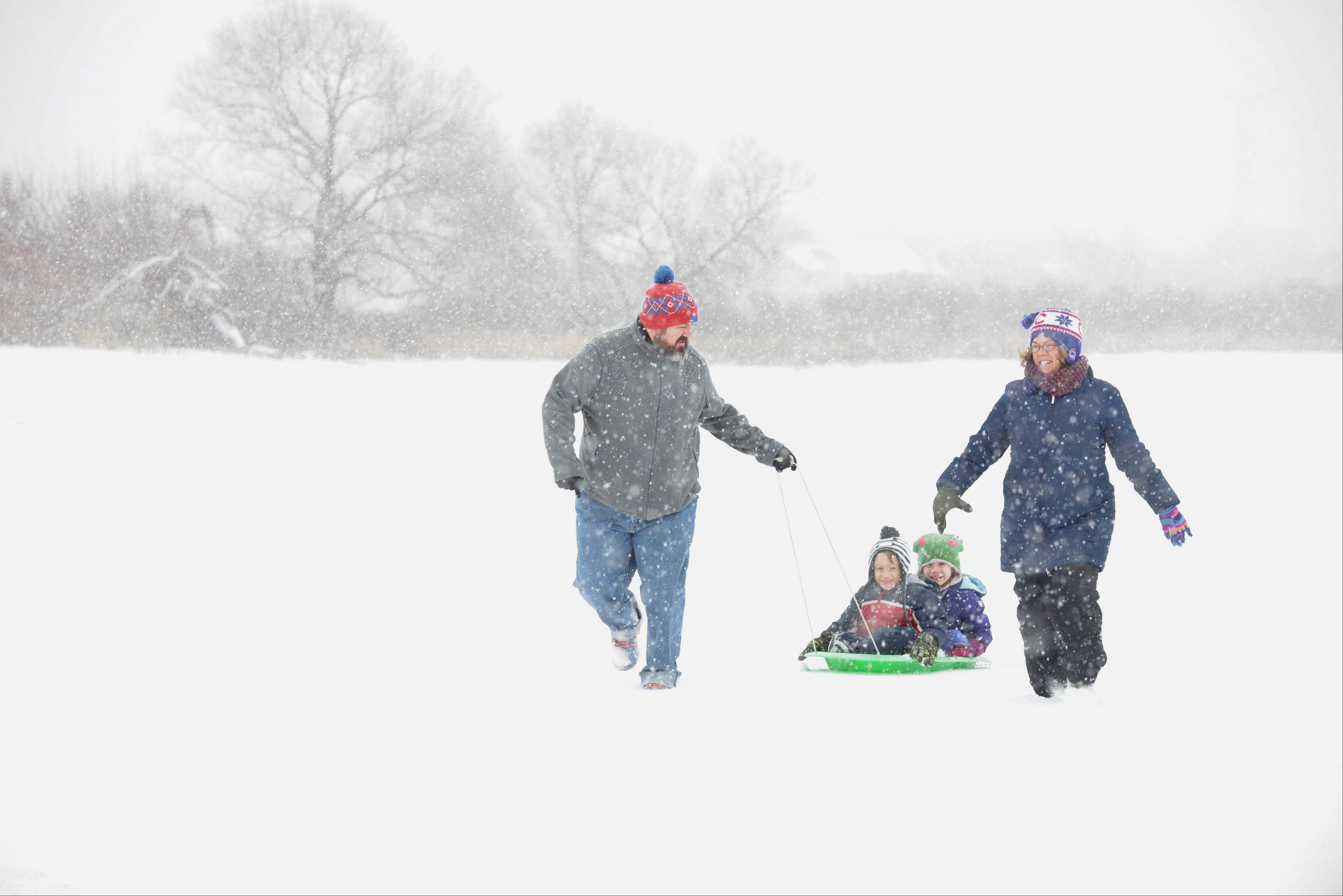 "Kevin and Eileen Woosley, of Aurora, pull their children Martin and Molly, both 6, through a snow covered field in Aurora Wednesday. ""It's like the snow is creating a fresh palette for the year to make an imprint on,"" Kevin commented."