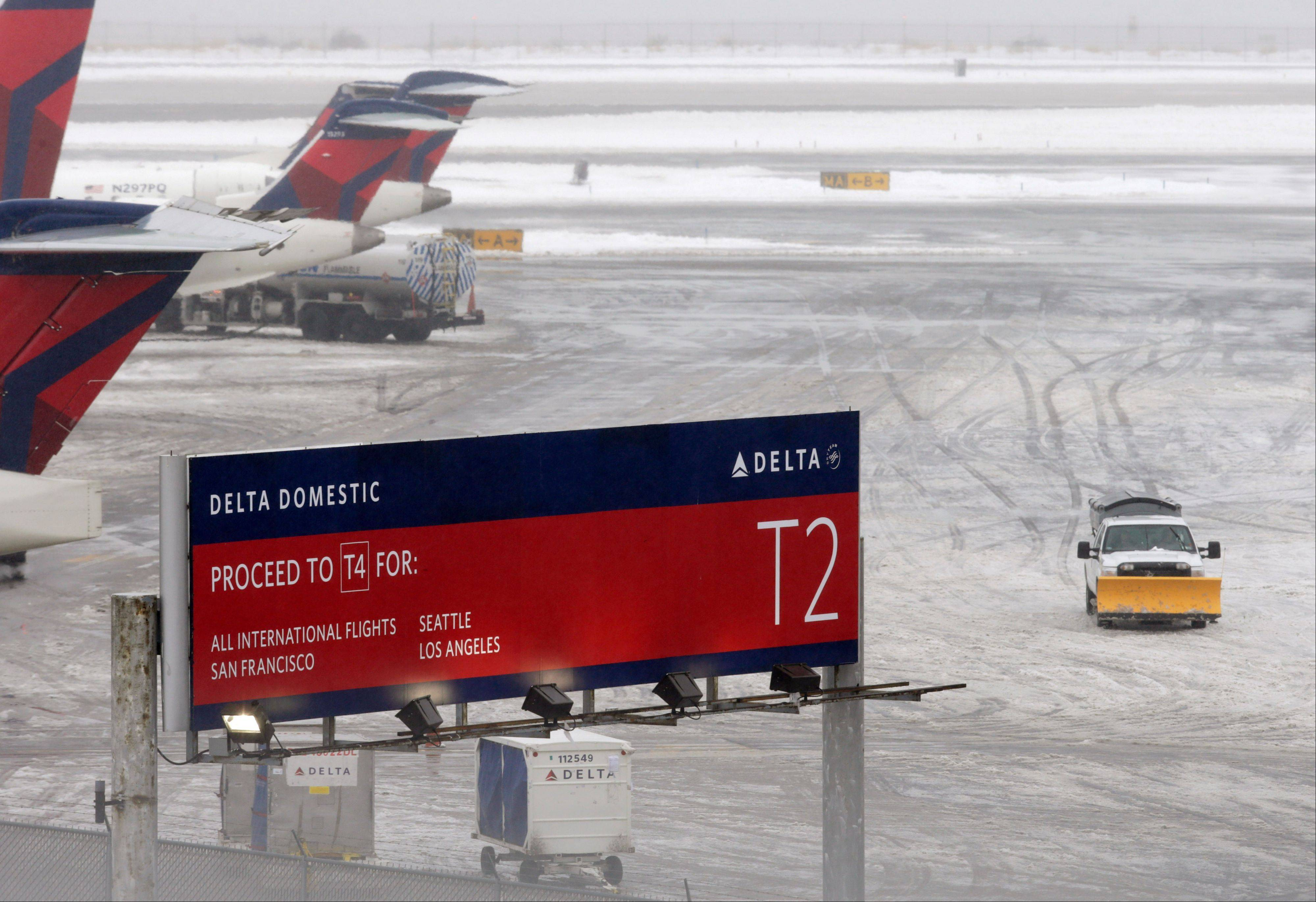 A snowplow makes its way on a slushy patch between two terminals after a Delta flight from Toronto to New York skidded off the runway into snow at Kennedy International Airport, temporarily halting all air travel into and out of the airport, Sunday in New York.