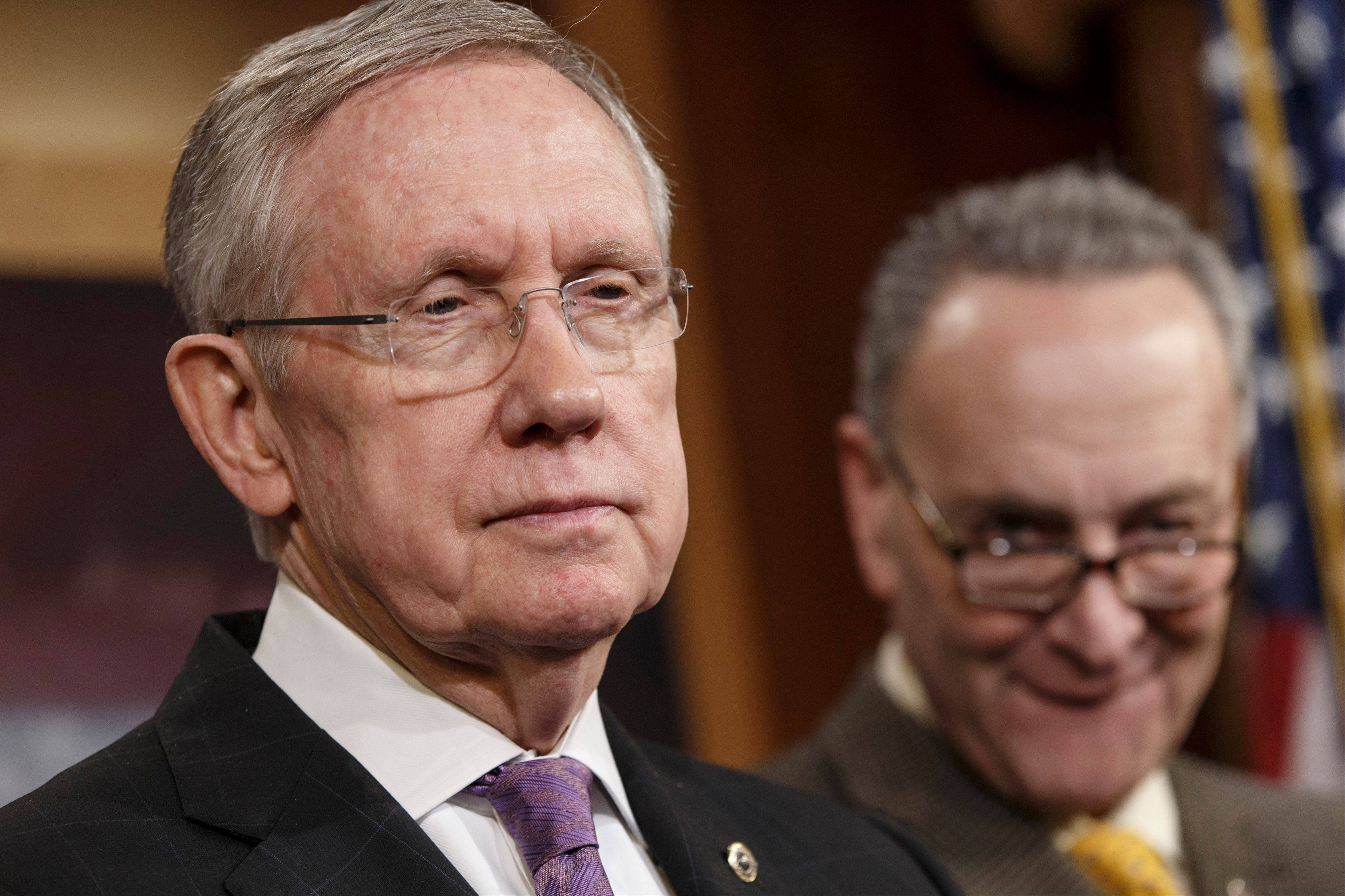Senate Majority Leader Harry Reid, left, accompanied by Sen. Charles Schumer, listens during a news conference on Capitol Hill in Washington last Dec. 16. Congress returns to work Monday with election-year politics certain to shape an already limited agenda.