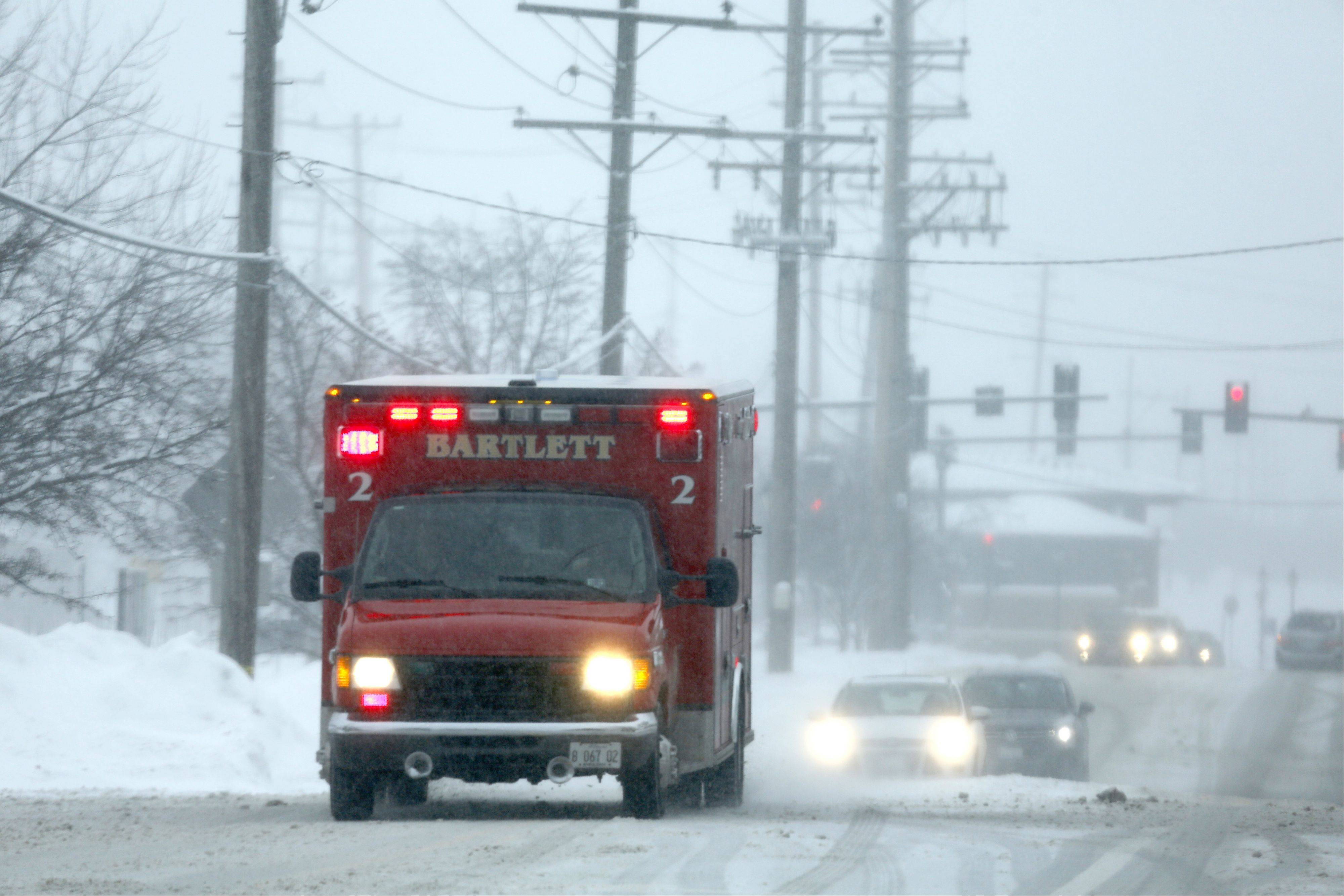 A Bartlett ambulance navigates the slippery conditions along Bartlett Road as a winter storm hit the area Sunday. Authorities reported numerous minor crashes across the suburbs Sunday.