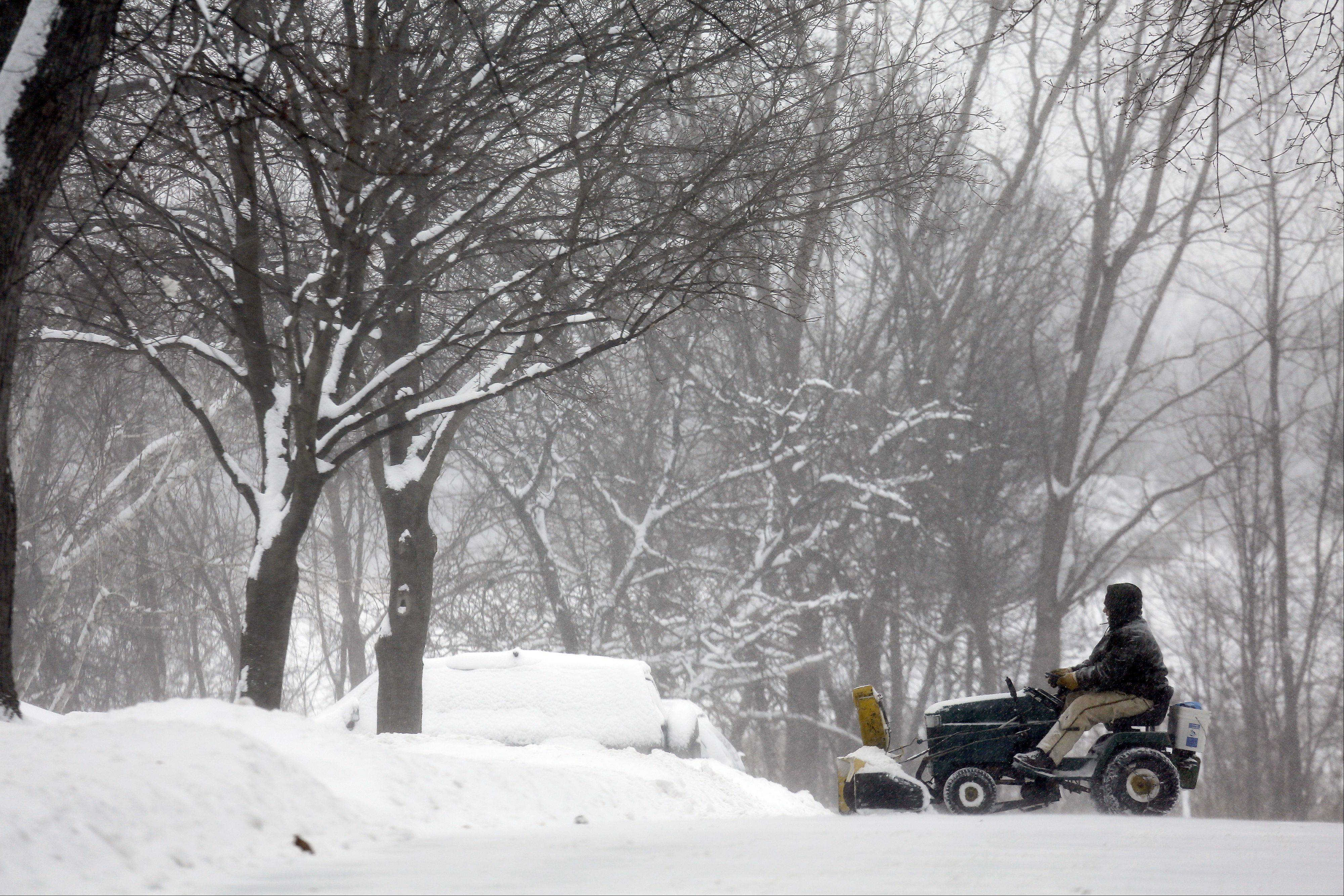 Tom Steele of Bartlett clears his neighbor's driveway Sunday as a winter storm dumped as many as 12 inches of snow on parts of the suburbs. Forecasters say dangerously cold temperatures will follow Monday, causing most suburban school district to call off Monday's classes.