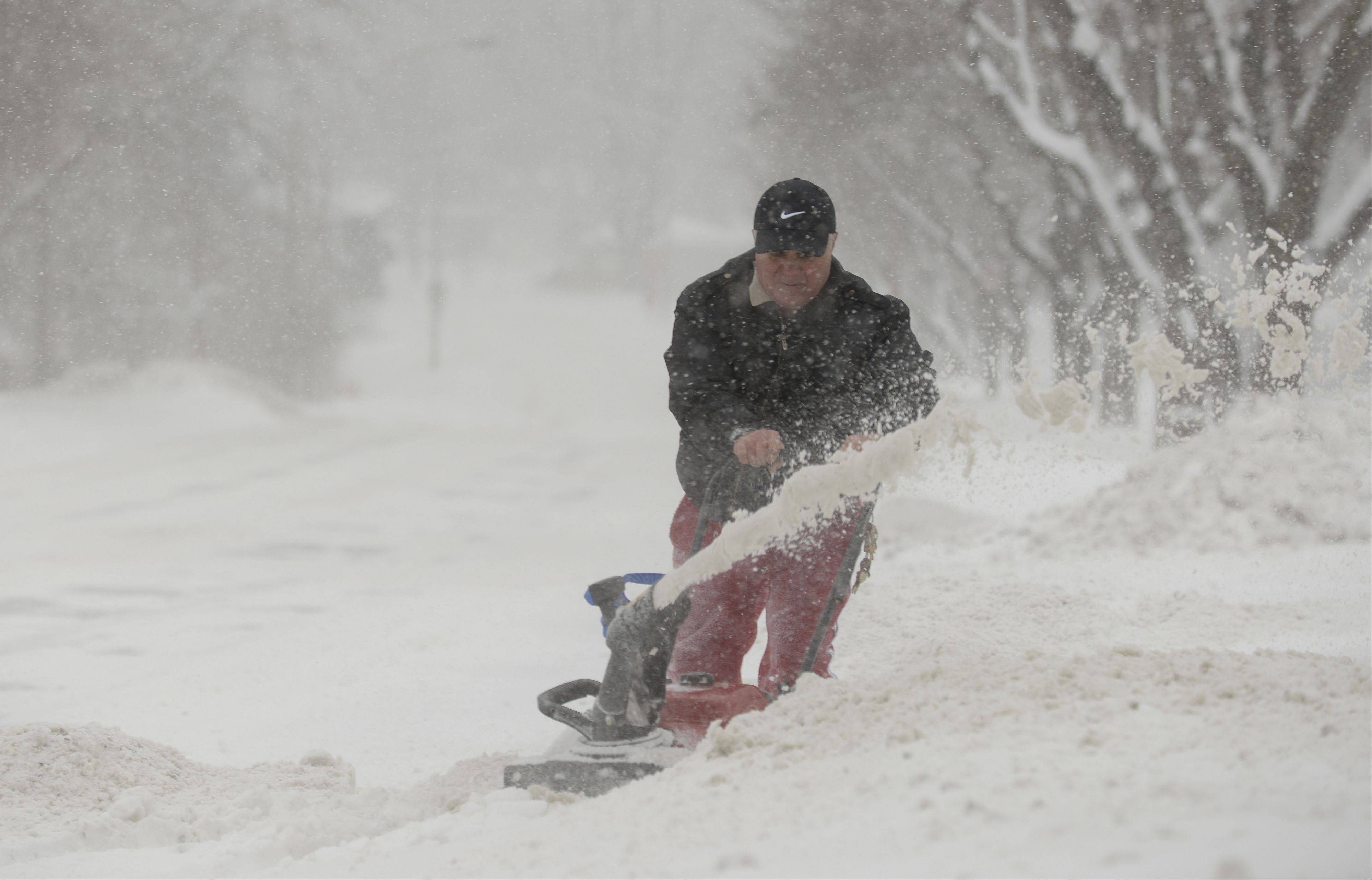 Koci Kocibelli of Lombard uses a snowblower to clear the snow off his driveway Sunday. The snow was expected to move out of the region by the end of the day, but brutally cold temperatures are expected to settle in behind it.