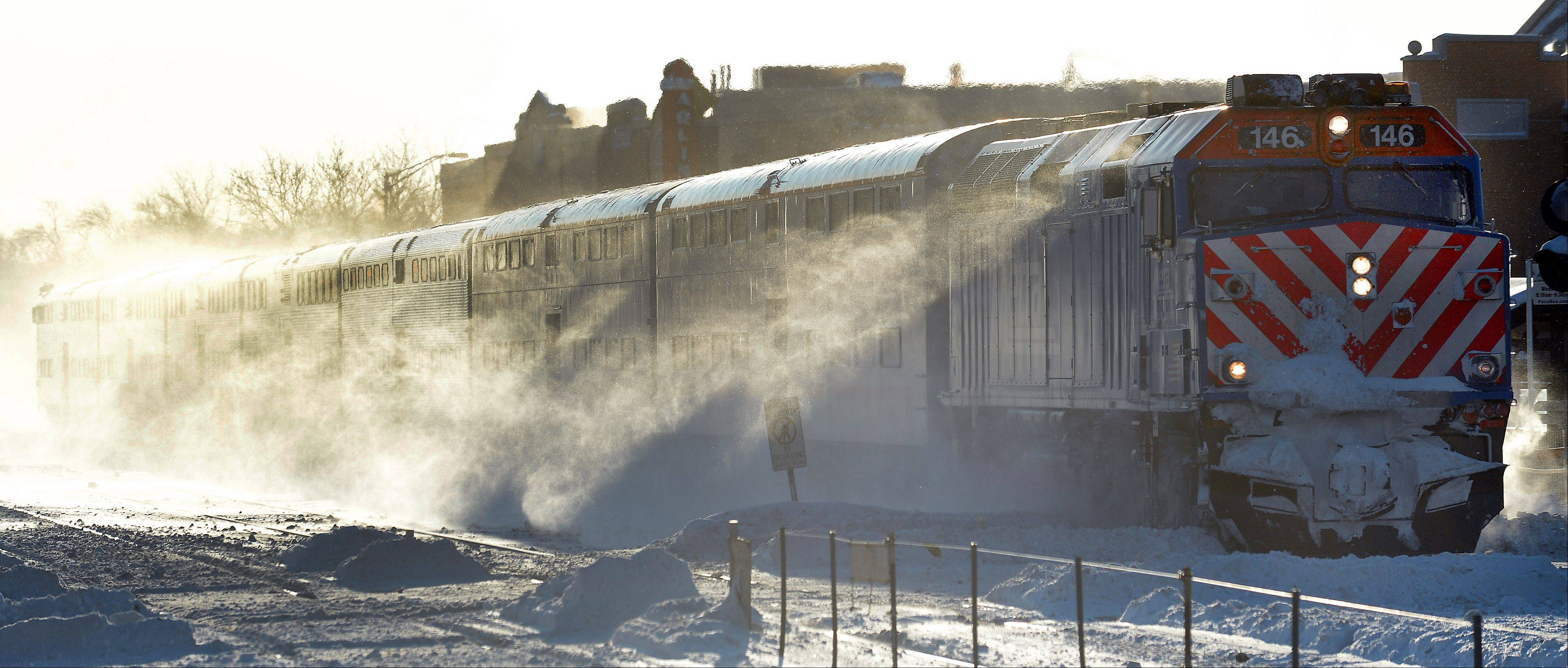 A Metra train plows its way through the blowing snow as it zips on by the Arlington Heights train station in subfreezing temperatures on Monday morning. Many suburban companies allowed employees to work from home Monday.