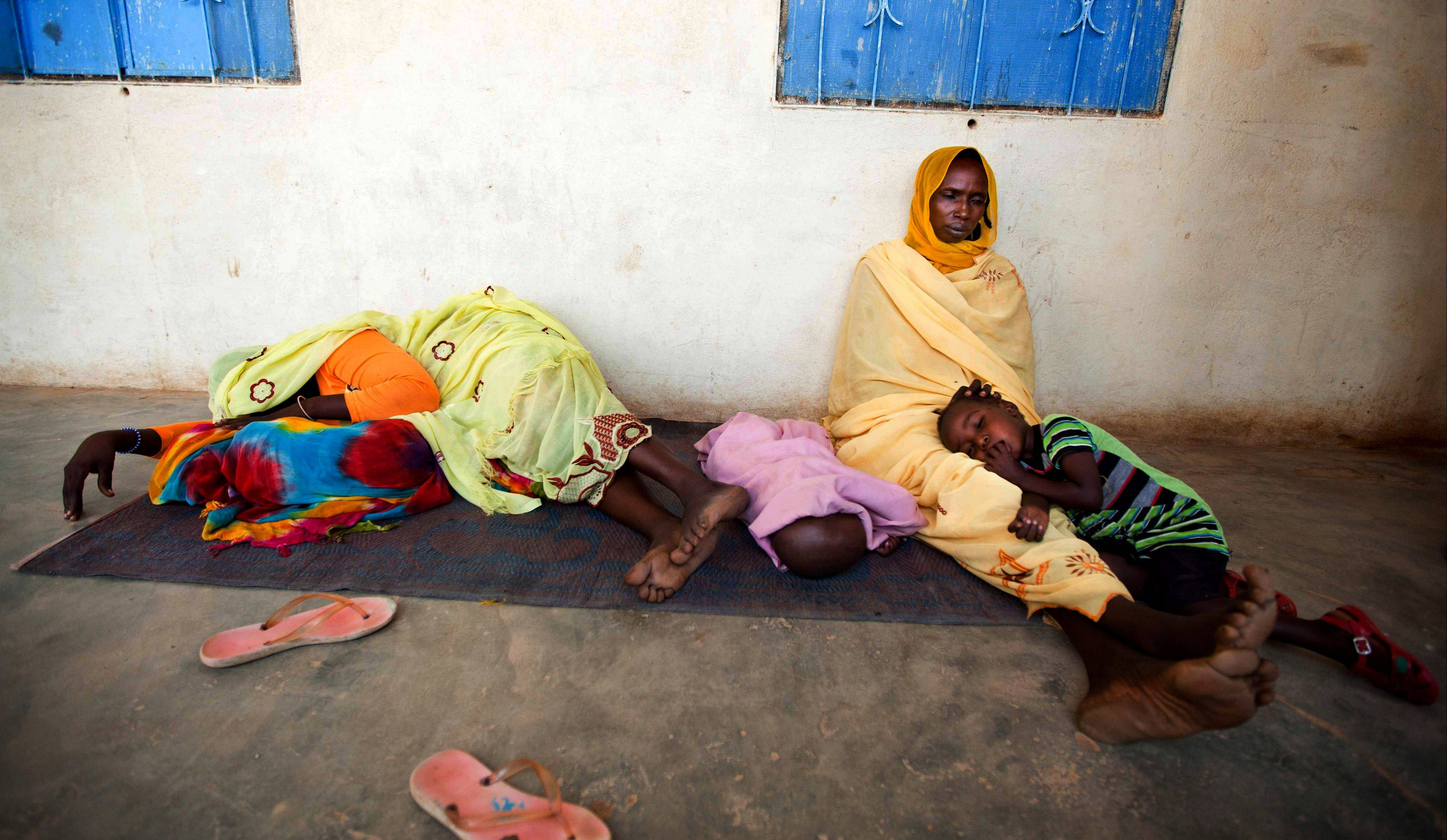 In this file photo released by the United Nations African Union Mission in Darfur, sick women and children wait to be treated at a hospital in El Sereif village, North Darfur, Sudan. Global efforts to curb malaria are stalling after a drop in funds to buy bed nets, according to a recent report from the World Health Organization.