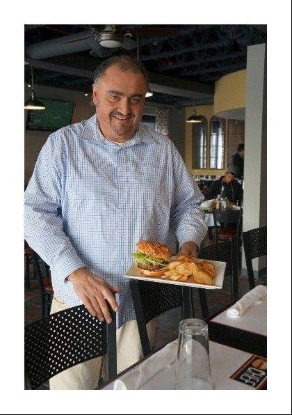 Cristiano Bassani, owner of the new Big Chef Burgers in Schaumburg, with the restaurant�s Spicy Burger. The restaurant opens Tuesday at 1602 E. Algonquin Road.