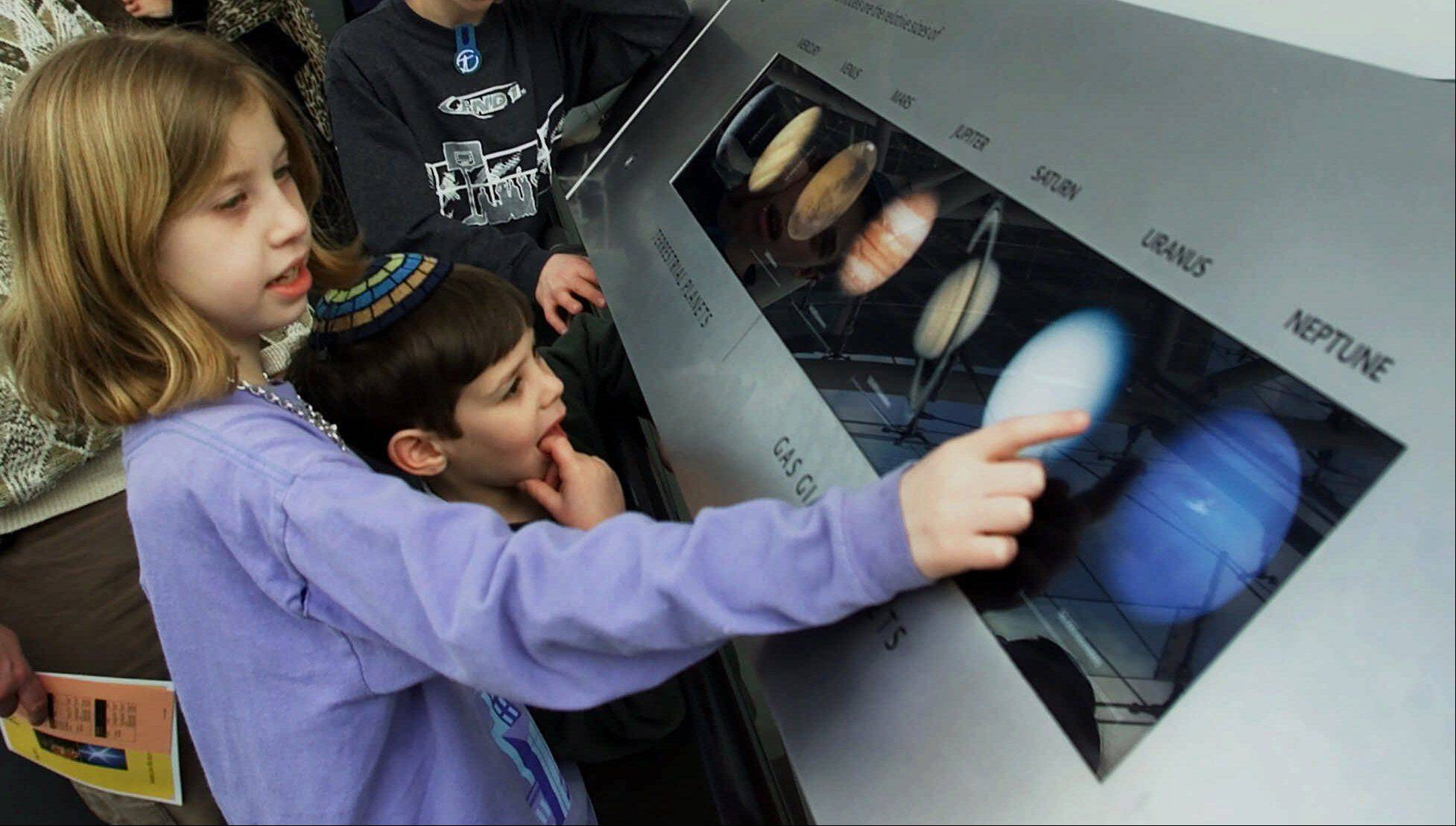 Tova Hagler, 10, left, reads through the names of the planets with her brother, Yaakov, 5, as they walk through the Scales of the Universe exhibit at the Rose Center for Earth and Space at the American Museum of Natural History in New York. Pluto was considered a planet from 1930 to 2006, but is now classified as a trans-Neptunian object.