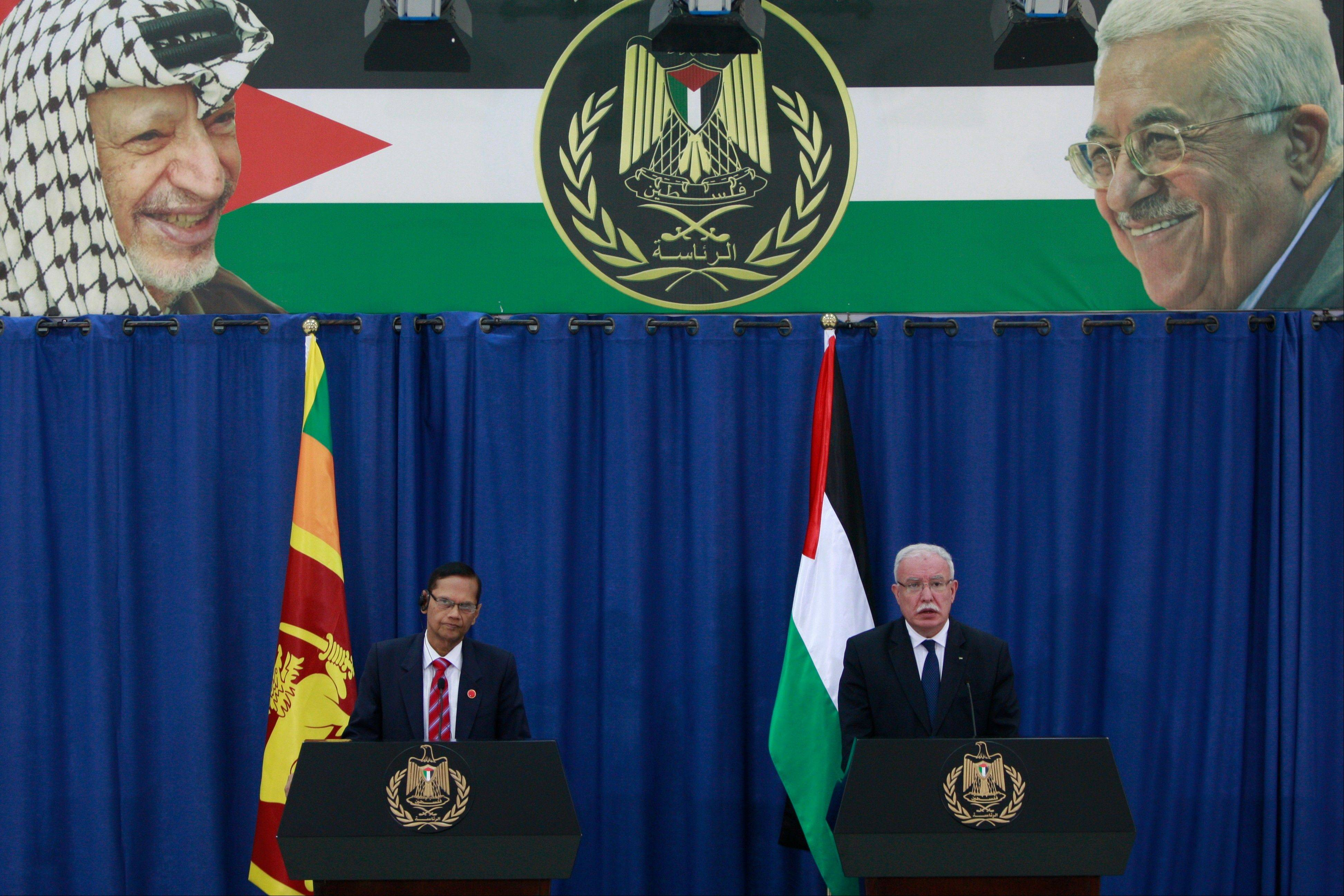 Sri Lanka�s foreign minister Gamini Peiris, left, with his Palestinian counterpart Riad al-Malki during a joint press conference in the West Bank city of Ramallah, Monday. Portraits of the late Palestinian leader, Yasser Arafat, left, and Palestinian President Mahmoud Abbas, right, are seen in a banner at top.