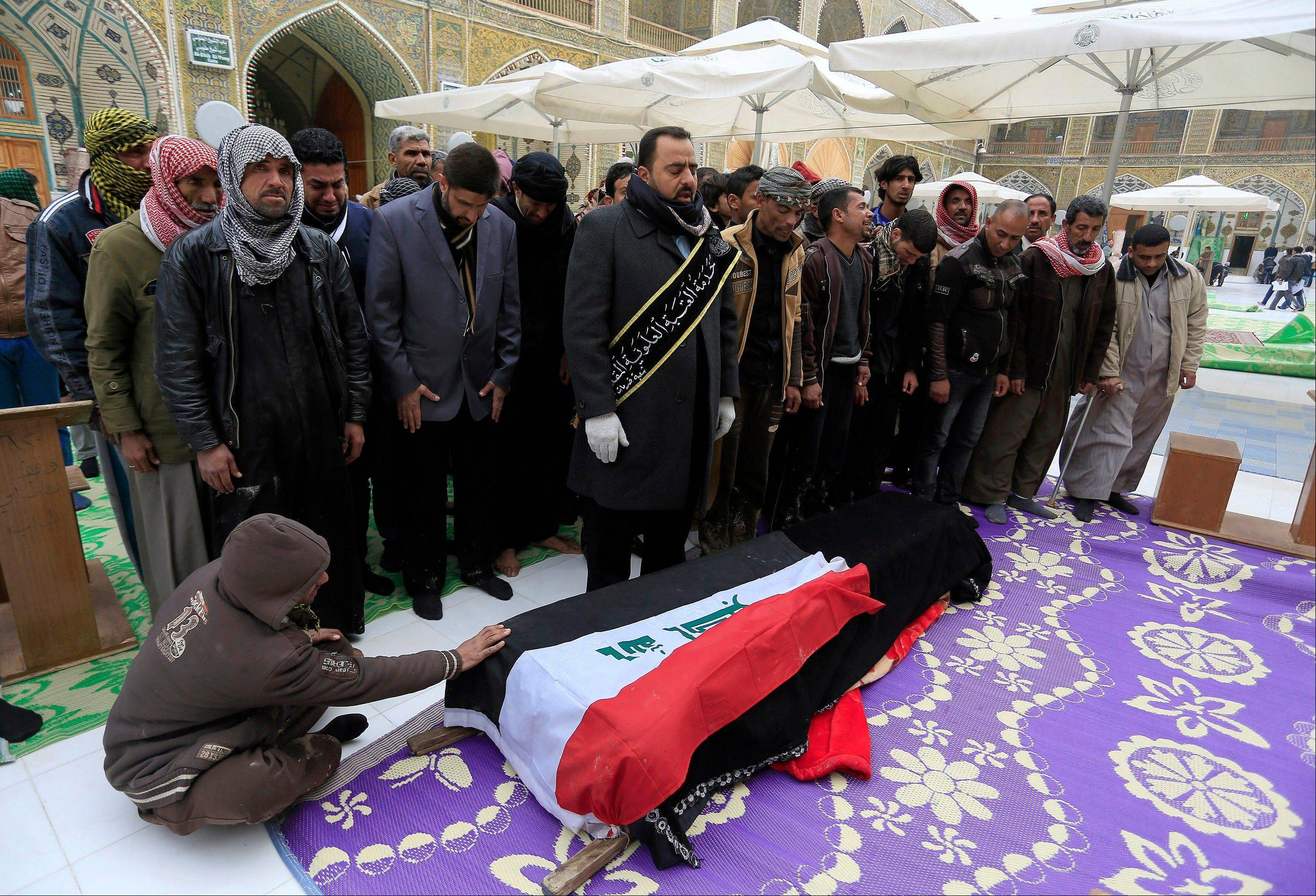 Mourners pray over the flag-draped coffin of Iraqi soldier Layth Ahmed, who was killed during the clashes in Ramadi, during his funeral procession in the Shiite holy city of Najaf, 100 miles south of Baghdad, Iraq, Monday,