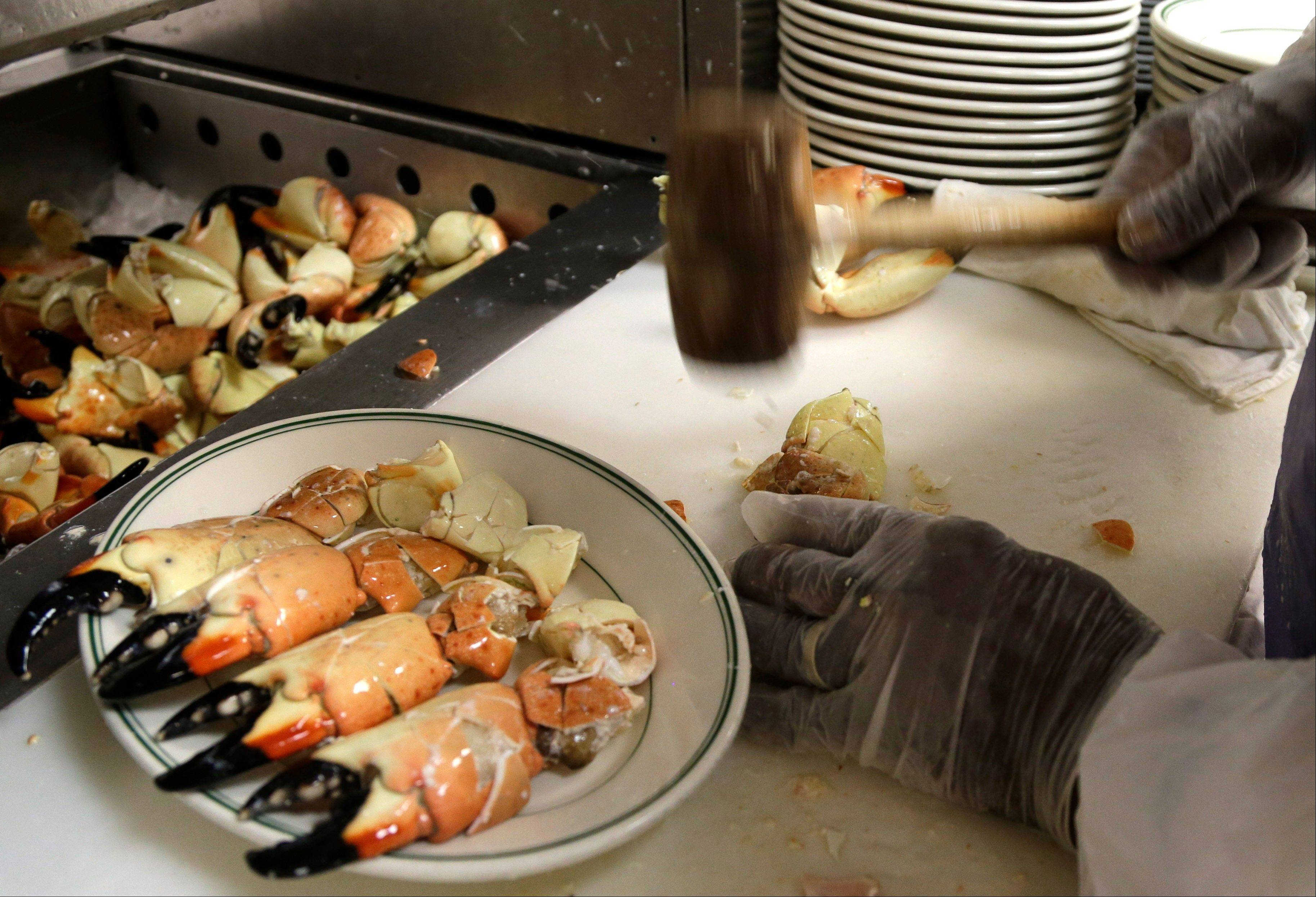 Eugene Green cracks stone crabs with a mallet while working in the kitchen at Joe's Stone Crab restaurant in Miami Beach, Fla. Green has worked for the family-owned restaurant for more than 40 forty years.