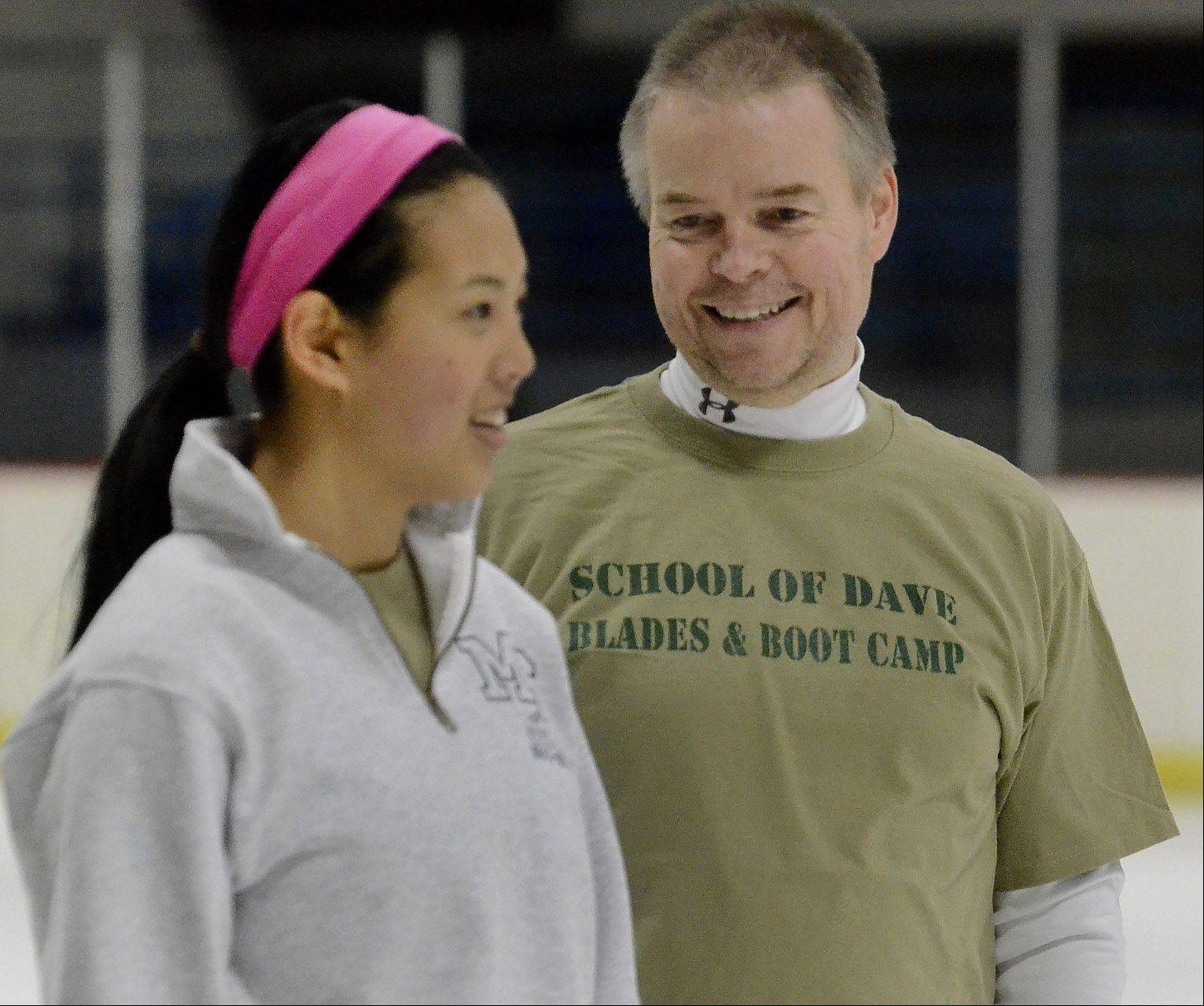 Former Olympic figure skater David Santee talks with Sarah Johnson of Park Ridge during his skating camp at the Oakton Ice Arena in Park Ridge.