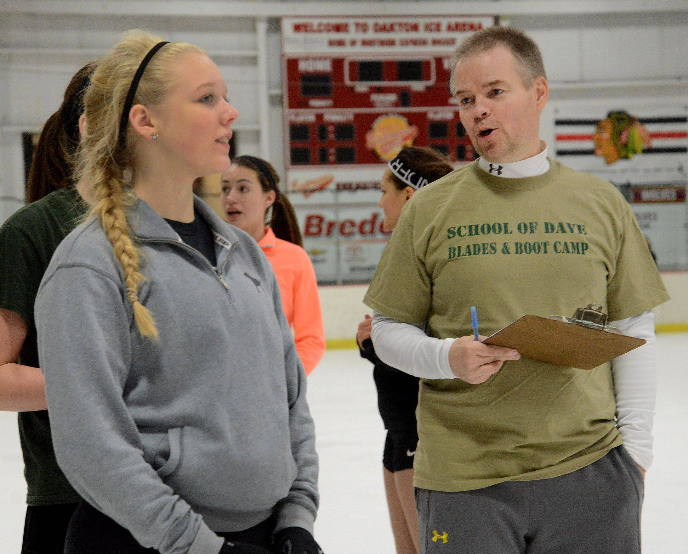 Former Olympic figure skater David Santee talks with Maggie Carey, left, of Park Ridge at his skating camp at the Oakton Ice Arena.