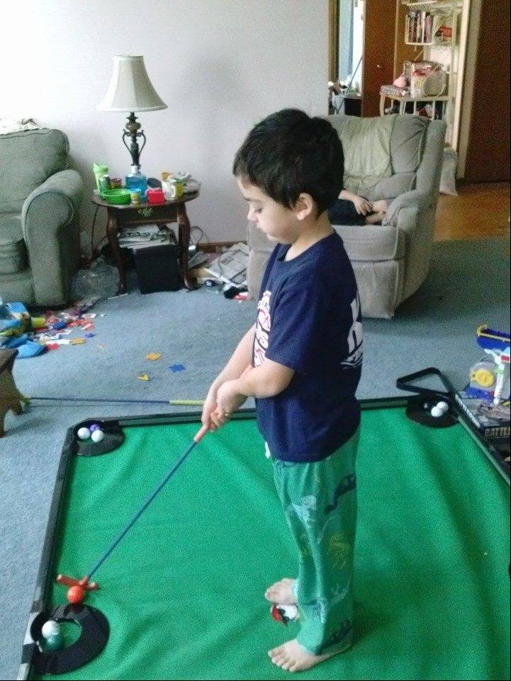 Damien Hlotke, 7, of Carol Stream, rides out Monday's arctic blast by practicing his short game in his grandmother's living room.