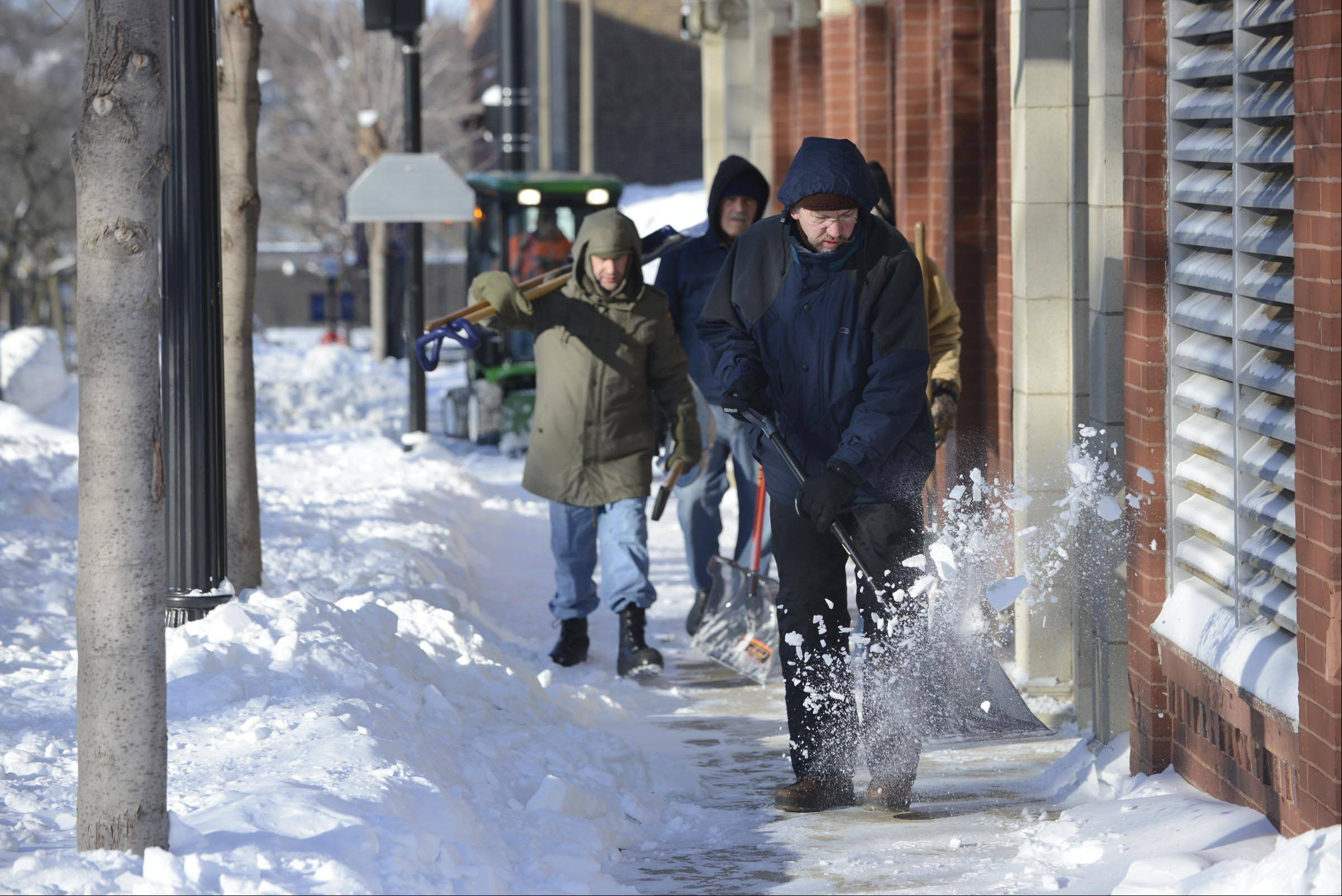 "Glen Ludwig works with ""The Crew""shoveling the sidewalks at St. John's Lutheran Church and school during Monday's freezing temperatures. ""Even though there is no school today, we keep it clean,"" he said. He and ""The Crew"" are trustees at the church at Division and Spring Streets in Elgin."