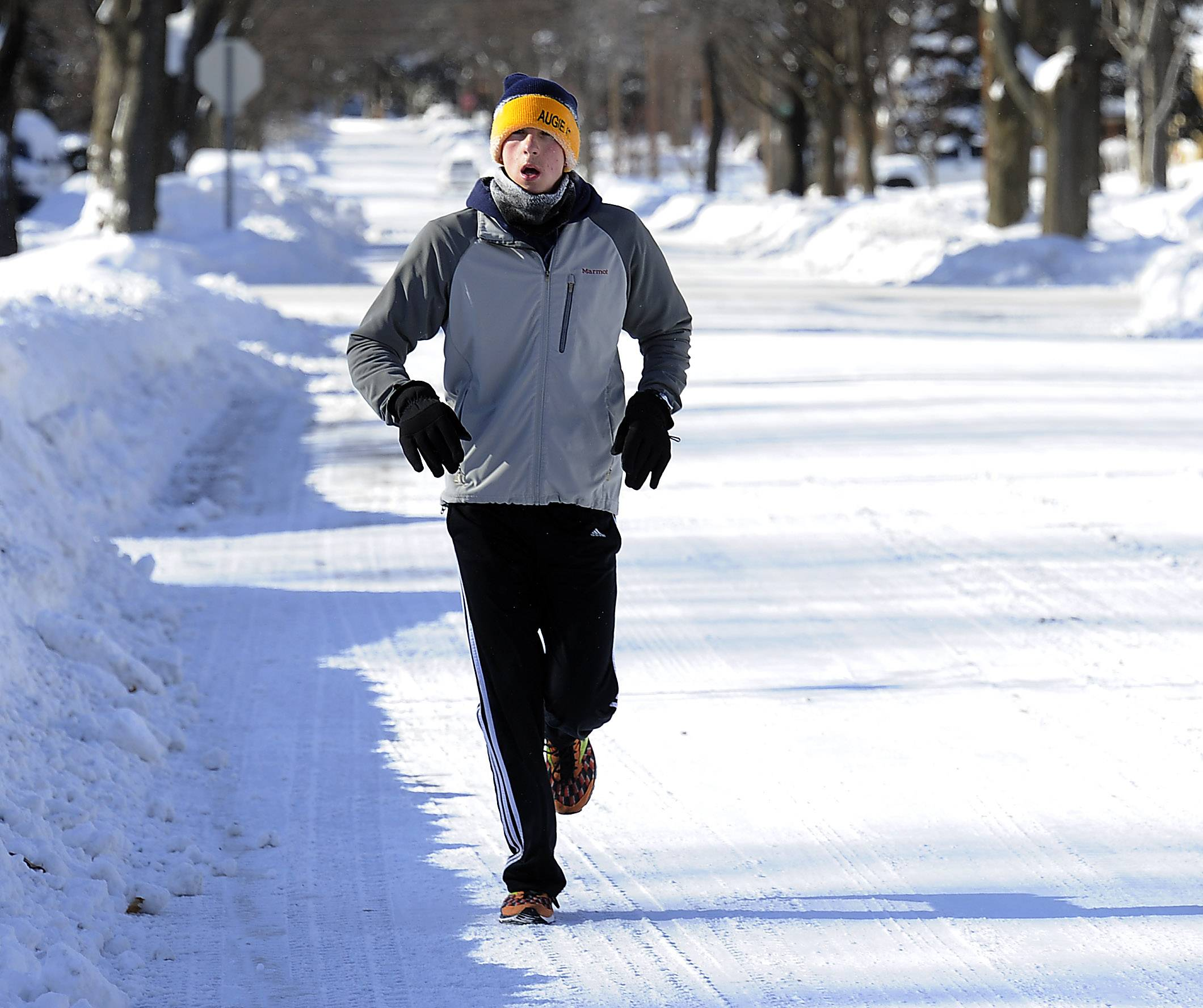 "Ethan Koch,19, of Mt. Prospect takes in a run saying ""its not that bad with enough layers on""  ""I am good to go."" as he winds his way up and down the streets."