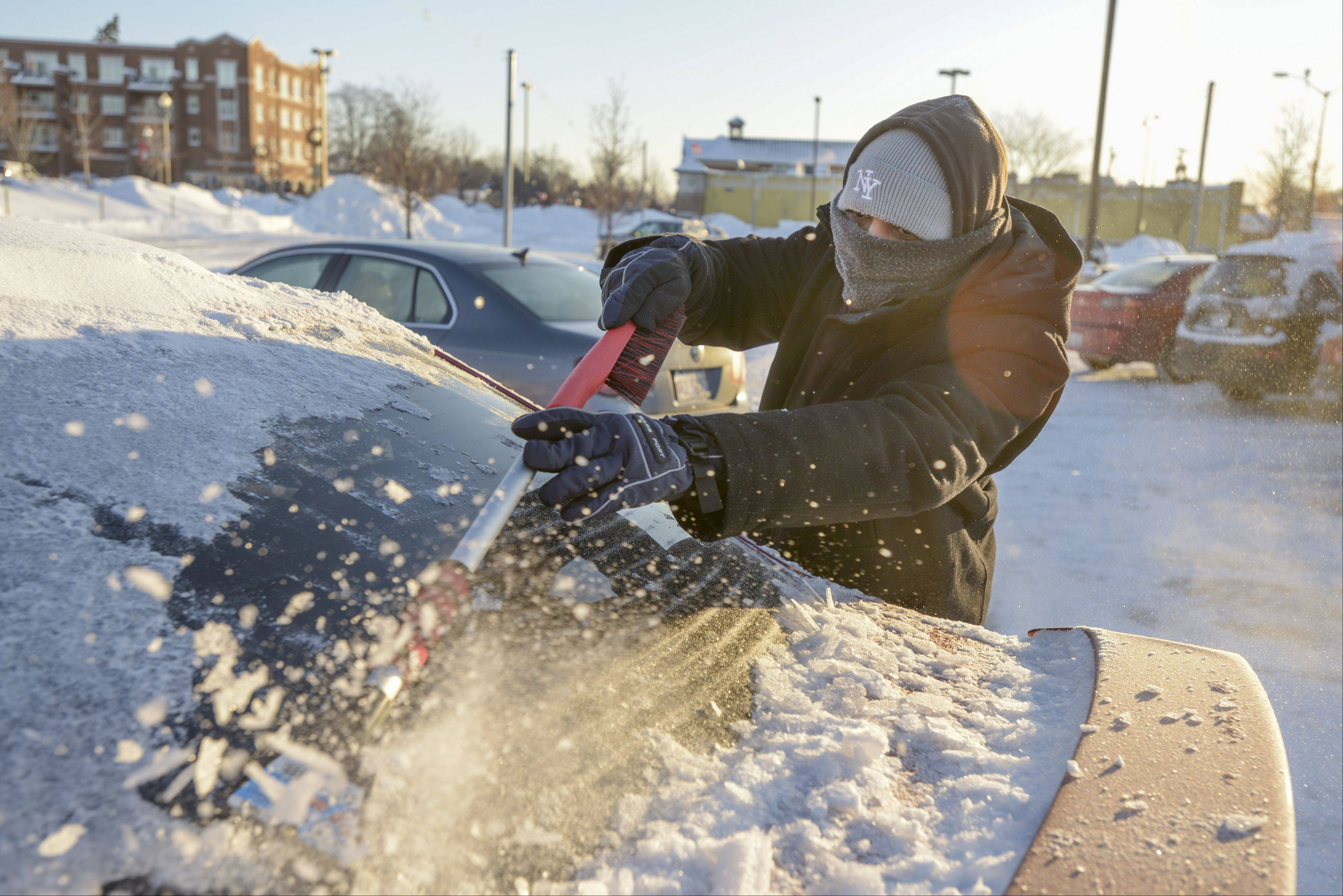 Viral Brahmbhatt of St. Charles clears the snow and ice off his car at the West Chicago train station after finding out via email that he could work from home today due to the record breaking extreme cold weather that has hit Chicago suburbs. That was a good thing for Brahmbhatt since his train was canceled due to the extreme cold.