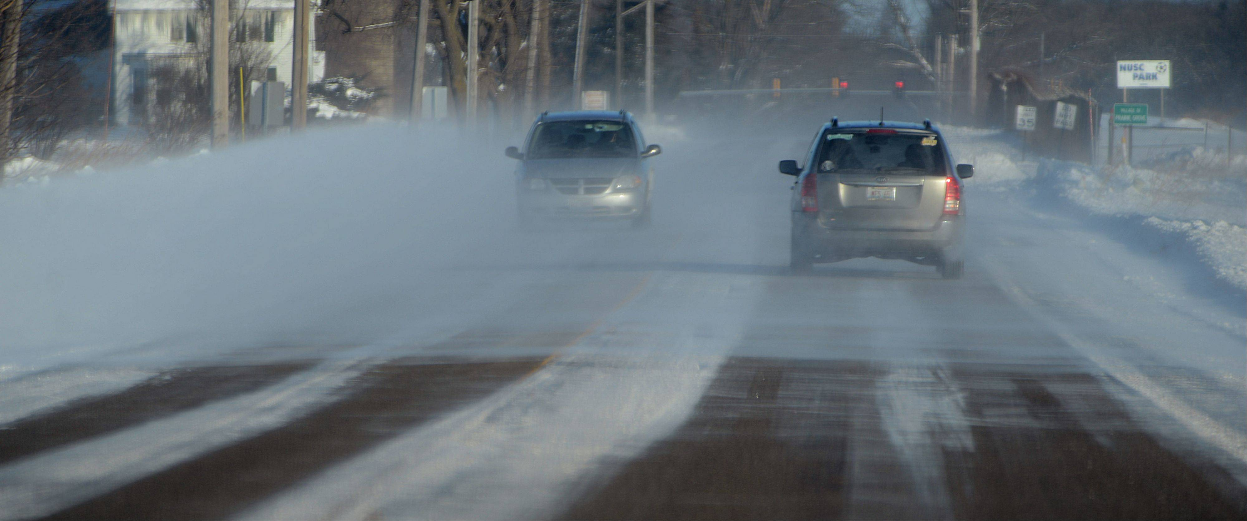 High winds blow snow across Valley View Road west of Island Lake impairing drivers' visibility Monday morning.