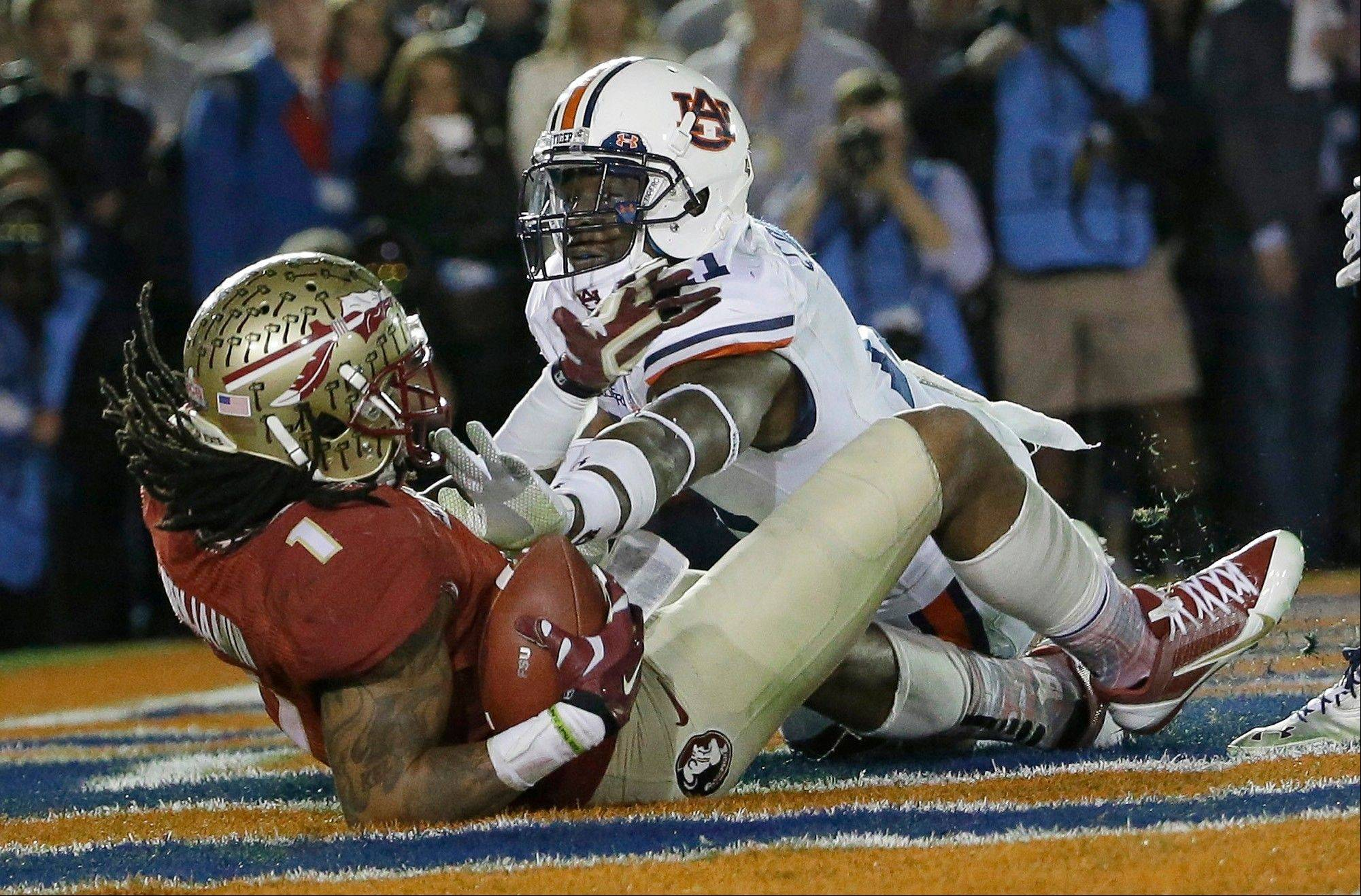Florida State's Kelvin Benjamin catches a touchdown pass in front of Auburn's Chris Davis during the second half of the NCAA BCS National Championship college football game Monday, Jan. 6, 2014, in Pasadena, Calif.