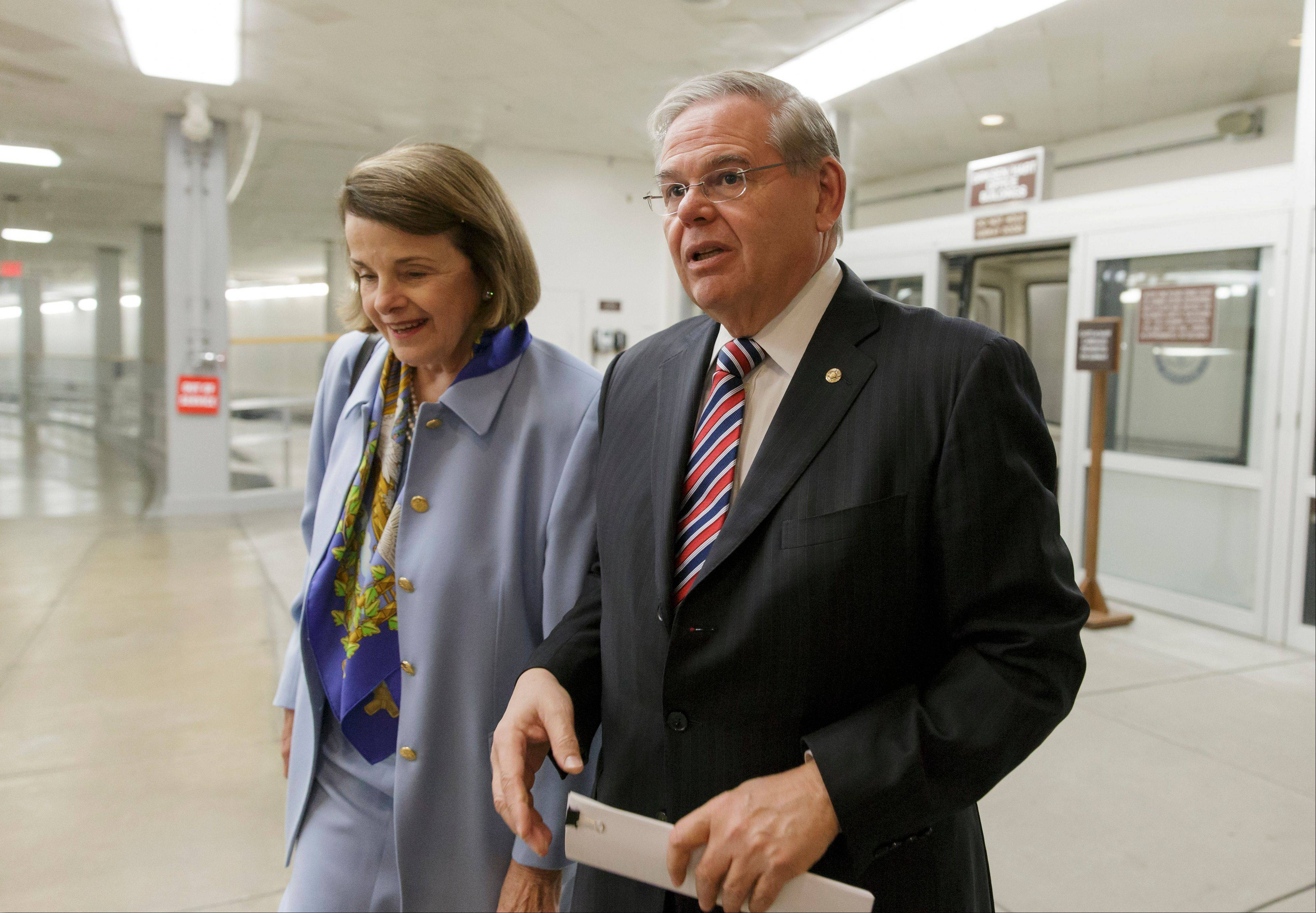 Sen. Dianne Feinstein, a California Democrat and chair of the Senate Intelligence Committee, left, and Senate Foreign Relations Chairman Robert Menendez, a New Jersey Democrat, right, walk together at the Capitol as lawmakers return from holiday recess on their way to scheduled votes, in Washington Monday.