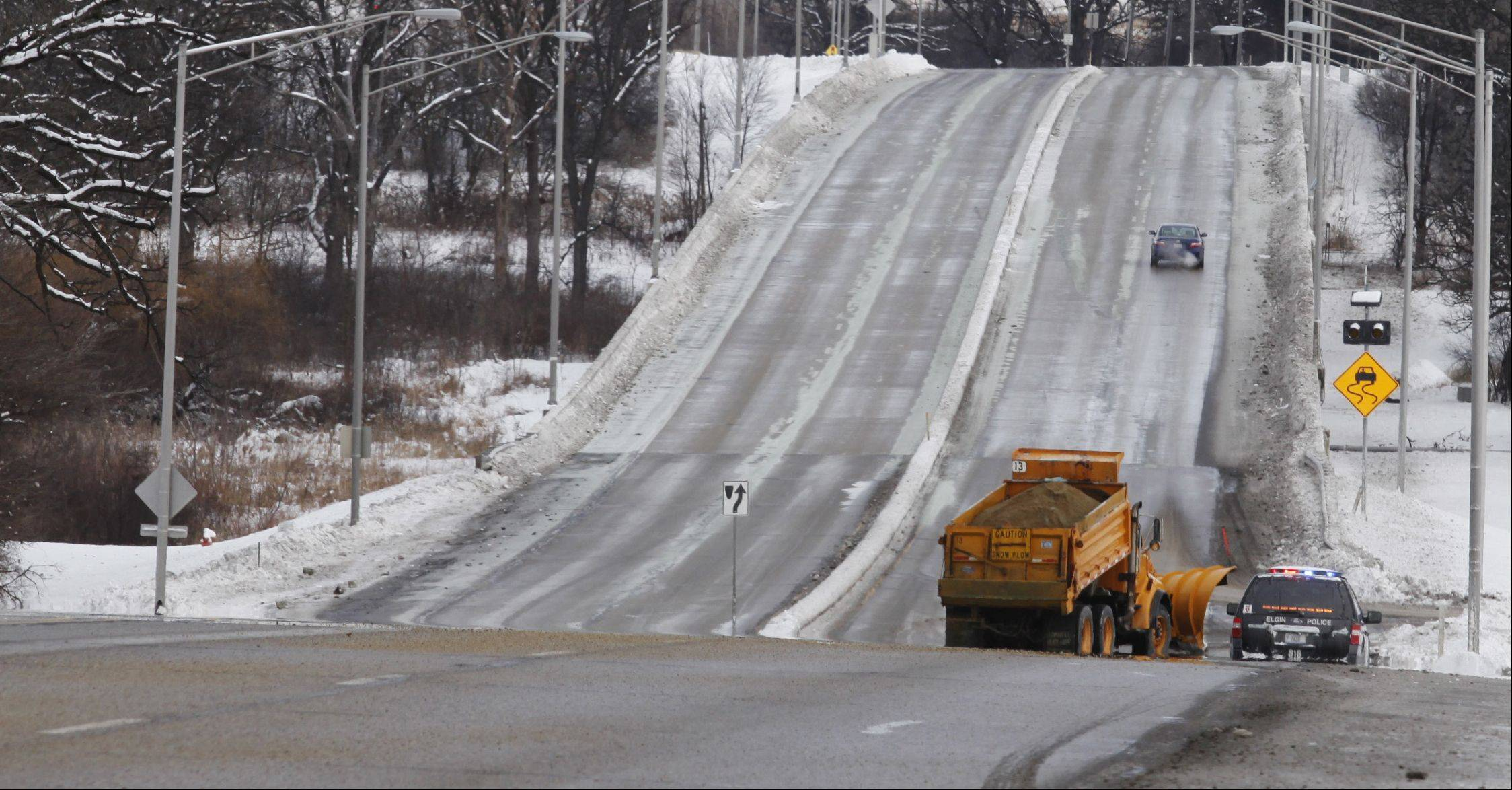 A snowplow helps clear up a problem spot on the northbound side of Randall Road north of Royal Boulevard Tuesday morning in Elgin, as icy conditions forced the closure of Randall Road from Royal to Big Timber Road.