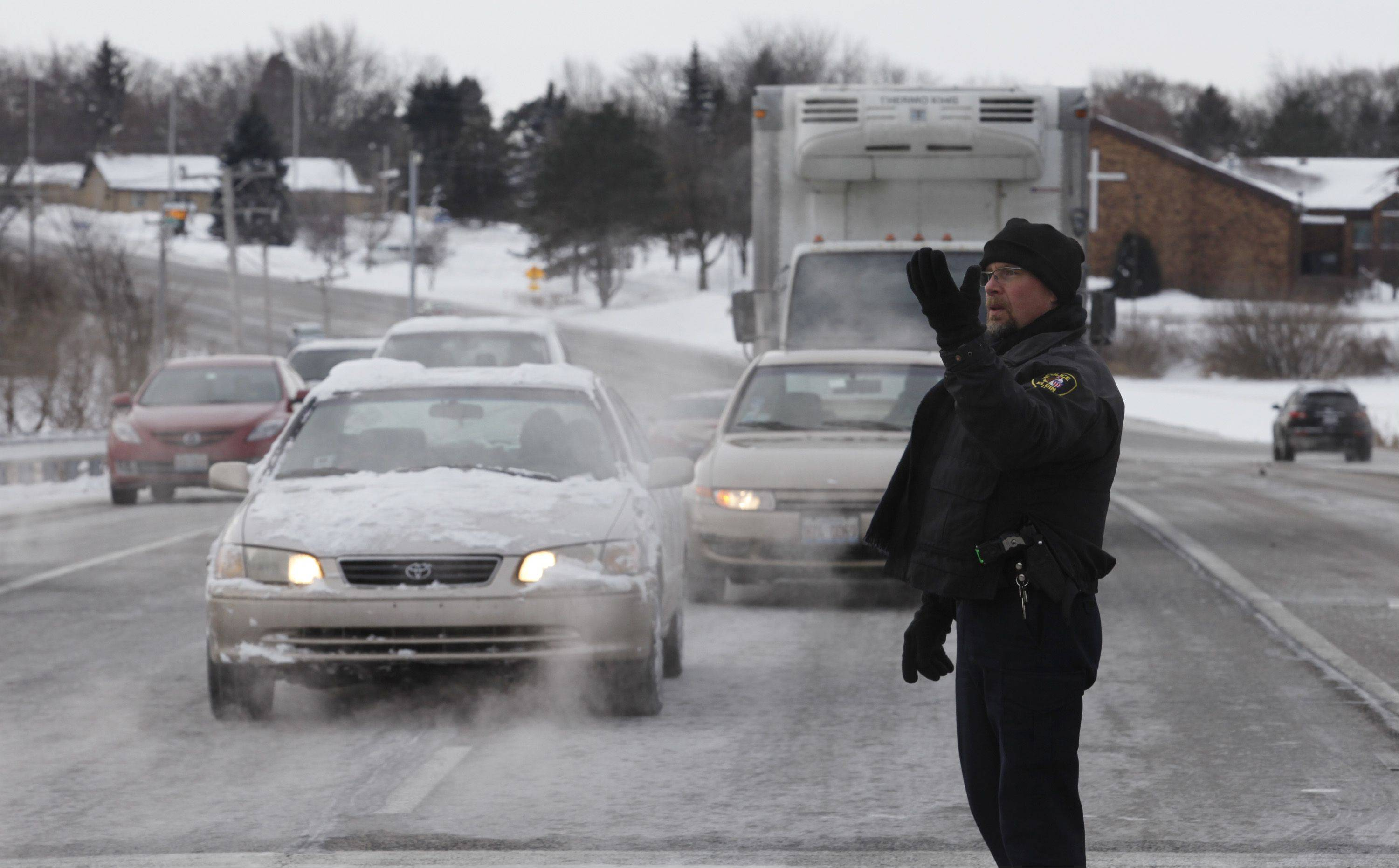 Elgin Police Officer Jeff Kendall diverts traffic from northbound Randall Road to eastbound Royal Boulevard Tuesday morning after icy conditions forced the closure of Randall Road from Royal to Big Timber Road.