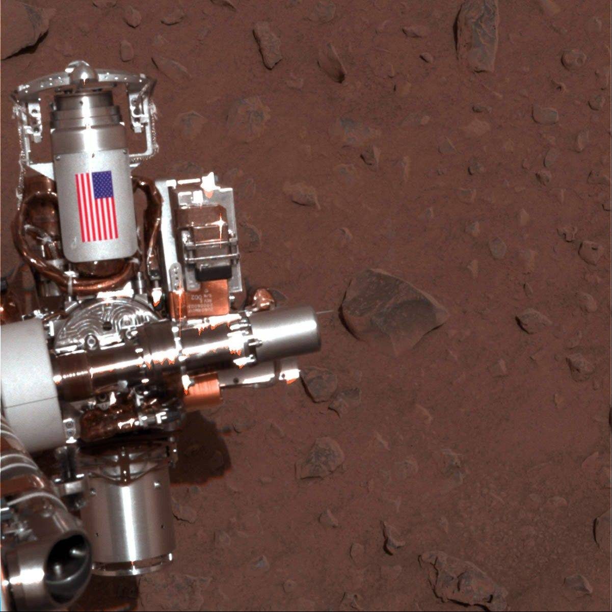 ASSOCIATED PRESS This image provided by NASA shows the piece of metal with the American flag on it is made of aluminum recovered from the site of the World Trade Center towers in New York City on Mars Rover Spirit that serves as a cable guard for Spiritís rock abrasion tool as well as a memorial to the victims of the Sept. 11, 2001, terrorist attacks.