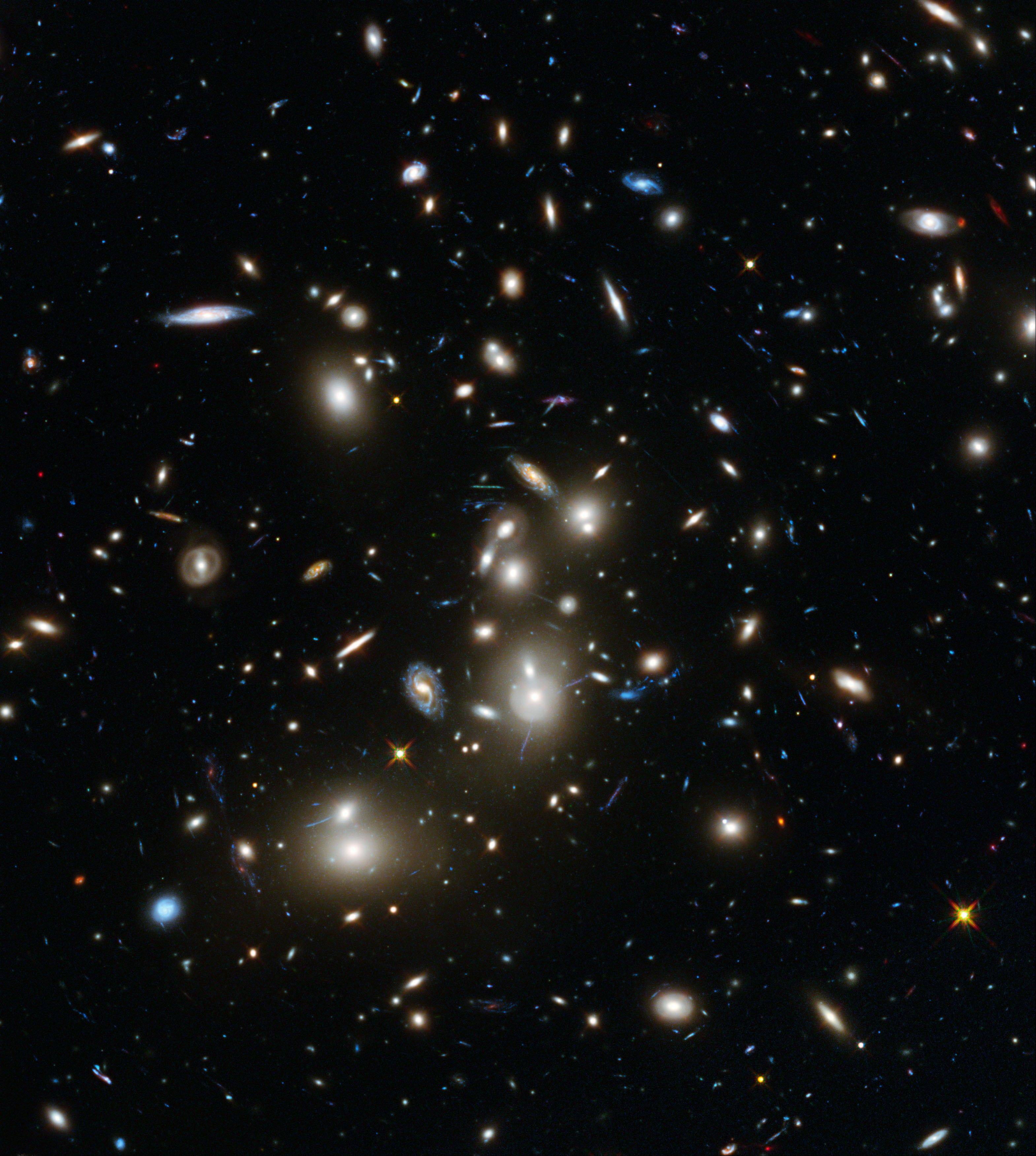 This undated image made available by the European Space Agency and NASA on Tuesday shows galaxies in the Abell 2744 cluster, and blue galaxies behind it, distorted and amplified by gravitational lensing. The long-exposure image taken with NASA�s Hubble Space Telescope shows some of the intrinsically faintest and youngest galaxies ever detected in visible light.