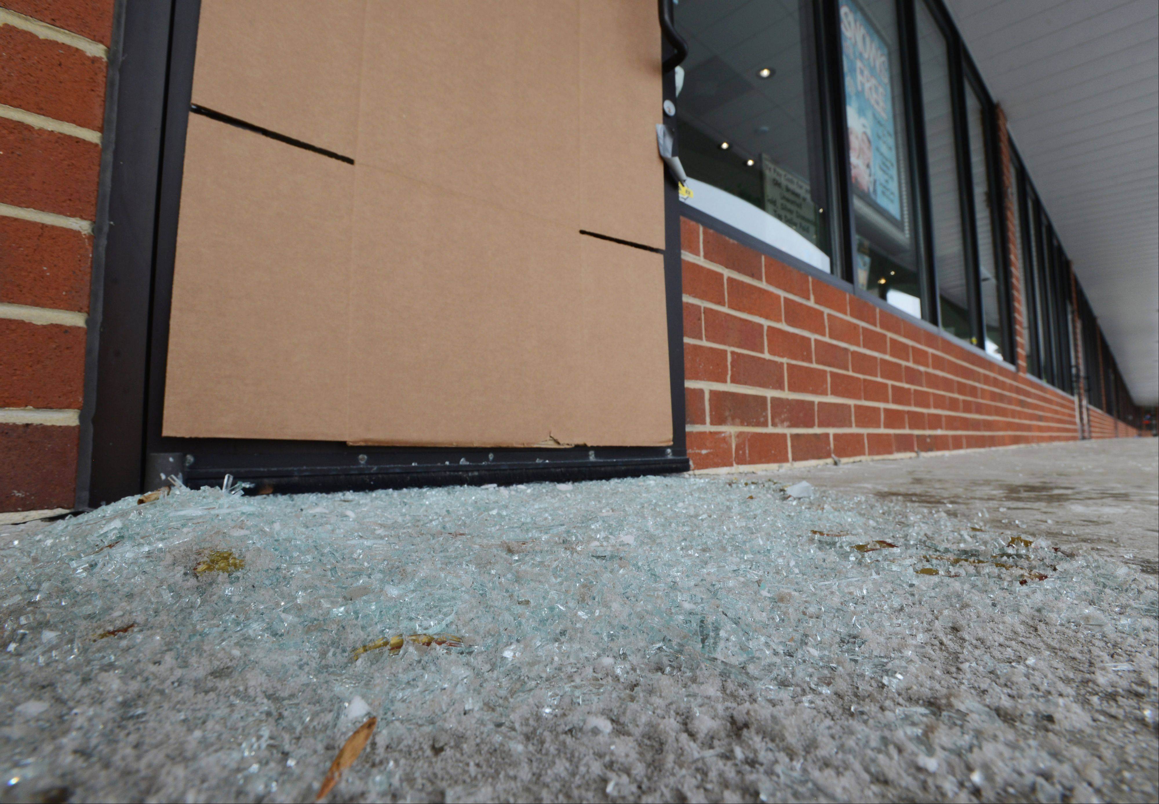 A pile of broken glass remains outside the main entrance to P.K. Bennett Jewelers in Mundelein Tuesday morning after burglars smashed the front door and several display cases before stealing merchandise inside the store. The store made headlines in recent days because of a New Year�s Day snow promotion.