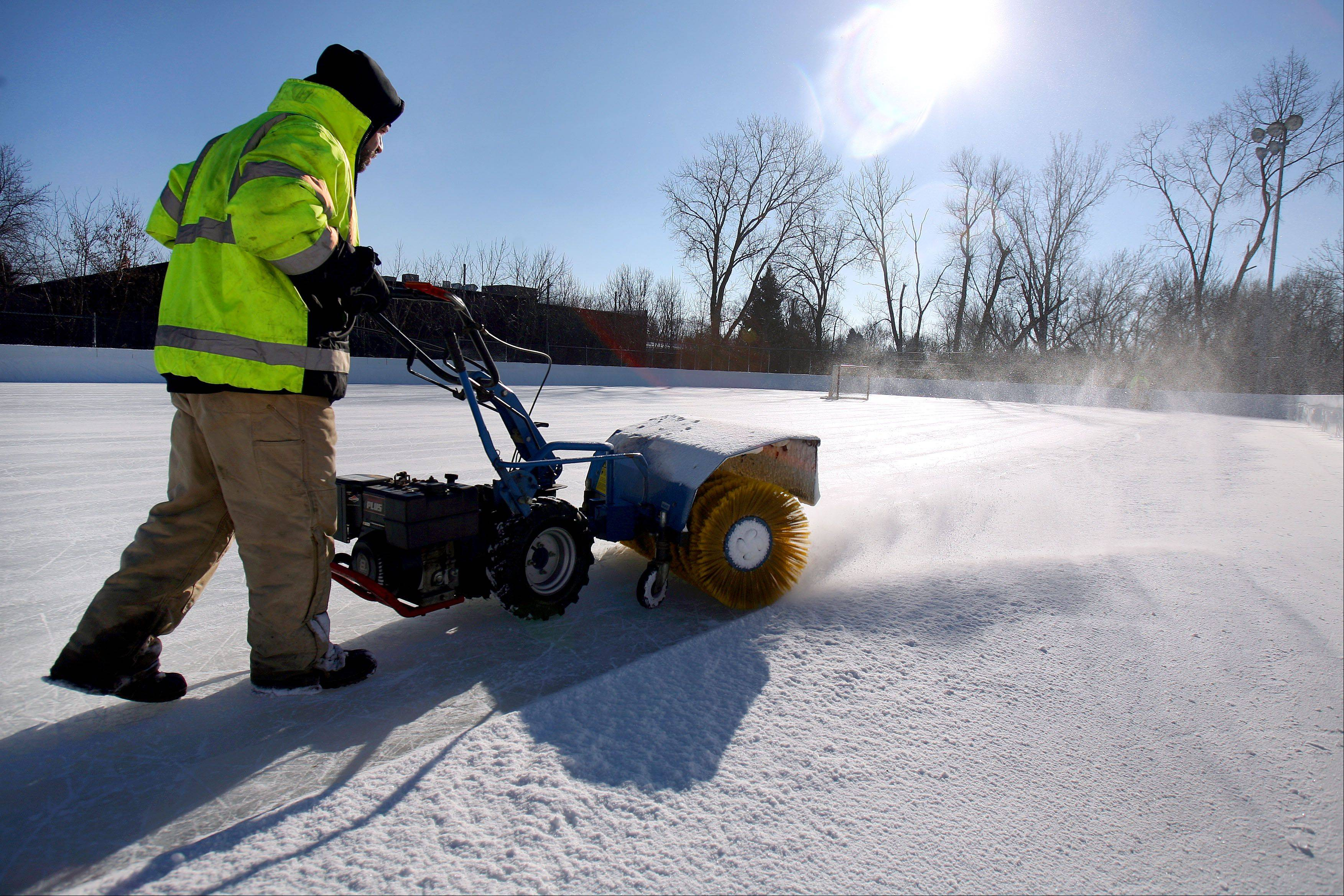 Libertyville Parks Department employee Rosalio Ayala clears the ice rink at Bolander Park in Libertyville earlier this season.