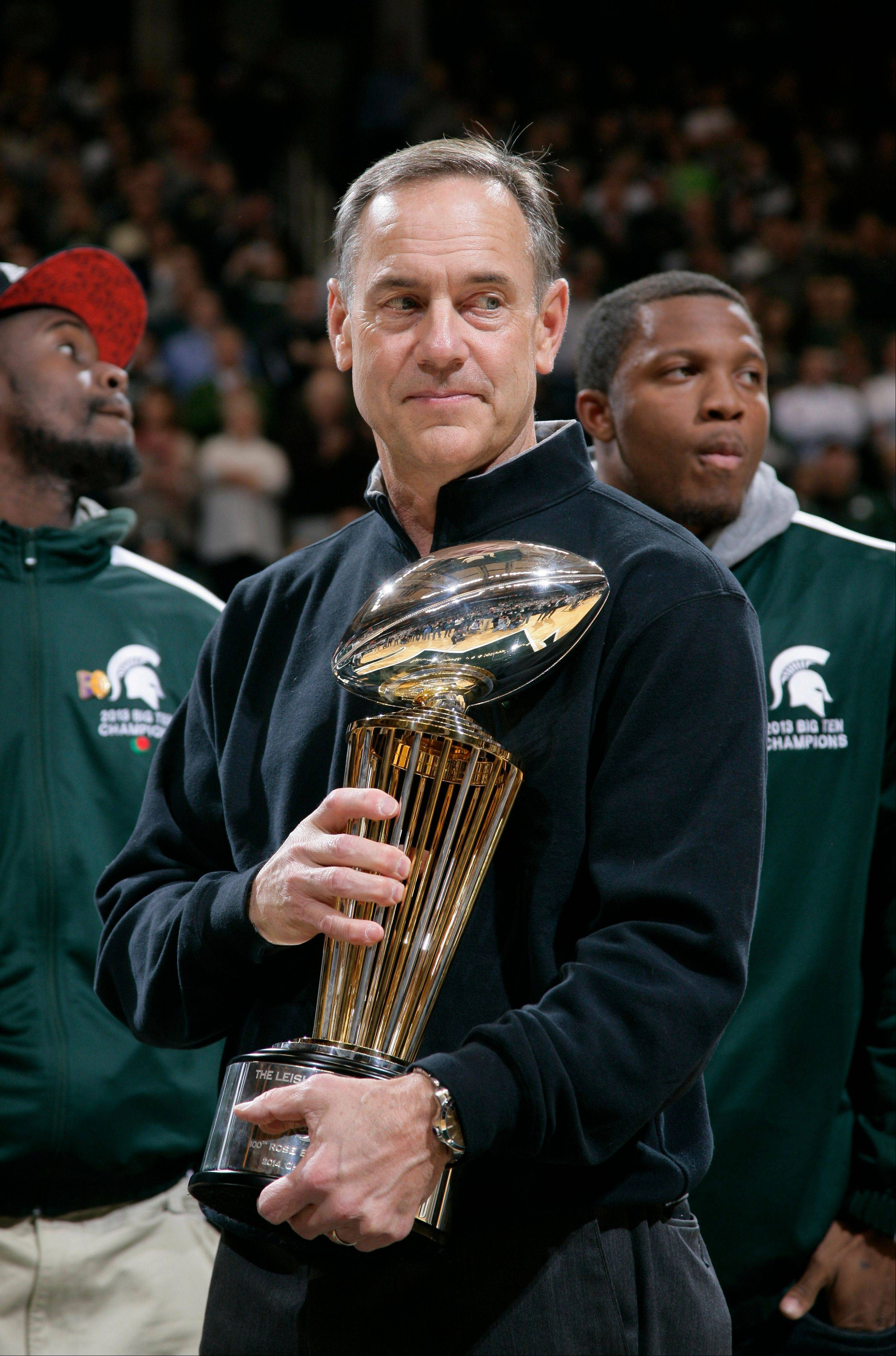 Michigan State football coach Mark Dantonio holds the 100th Rose Bowl championship trophy at a basketball game between Michigan State and Ohio State on Tuesday in East Lansing, Mich.