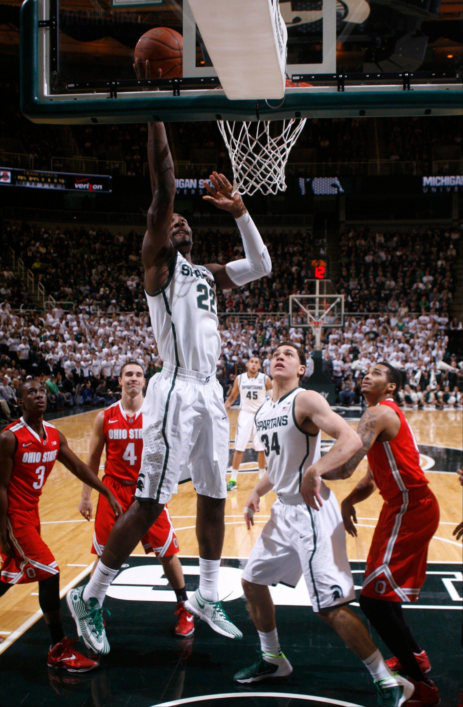 Michigan State�s Branden Dawson lays the ball up as Ohio State�s Shanon Scott (3), Aaron Craft (4), and LaQuinton Ross, right, and Michigan State�s Gavin Schilling watch during the first half Tuesday in East Lansing, Mich.