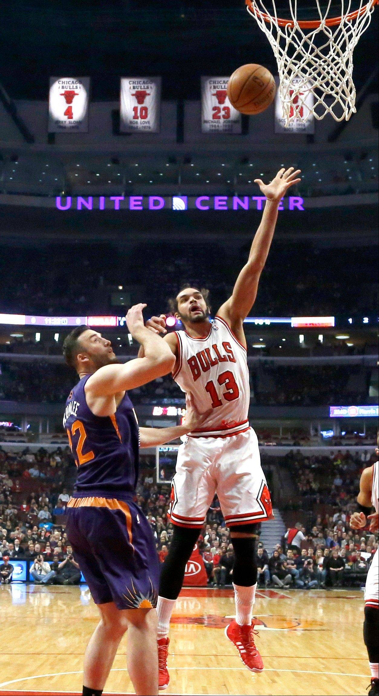 Chicago Bulls center Joakim Noah (13) shoots over Phoenix Suns center Miles Plumlee during the first half of an NBA basketball game, Tuesday, Jan. 7, 2014, in Chicago. (AP Photo/Charles Rex Arbogast)