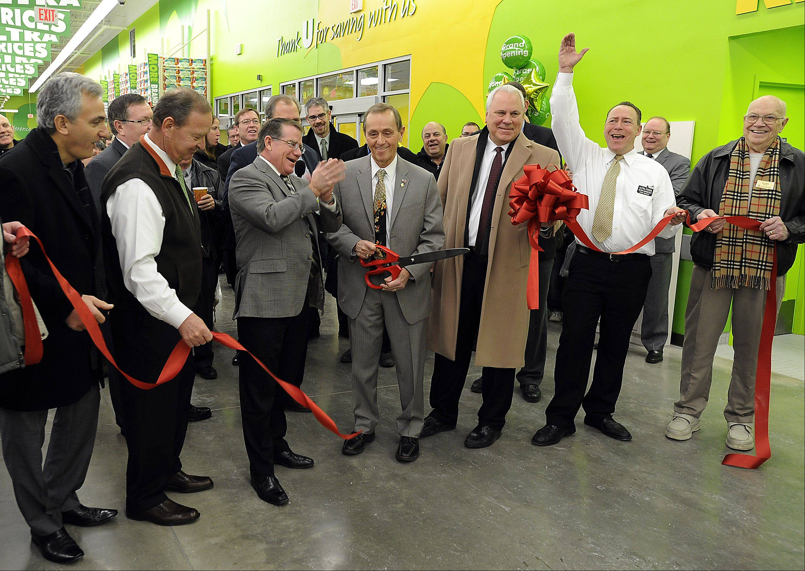 Prospect Heights Mayor Nicholas Helmer, center, cuts the ribbon at the grand opening of the new Ultra Foods Tuesday morning.