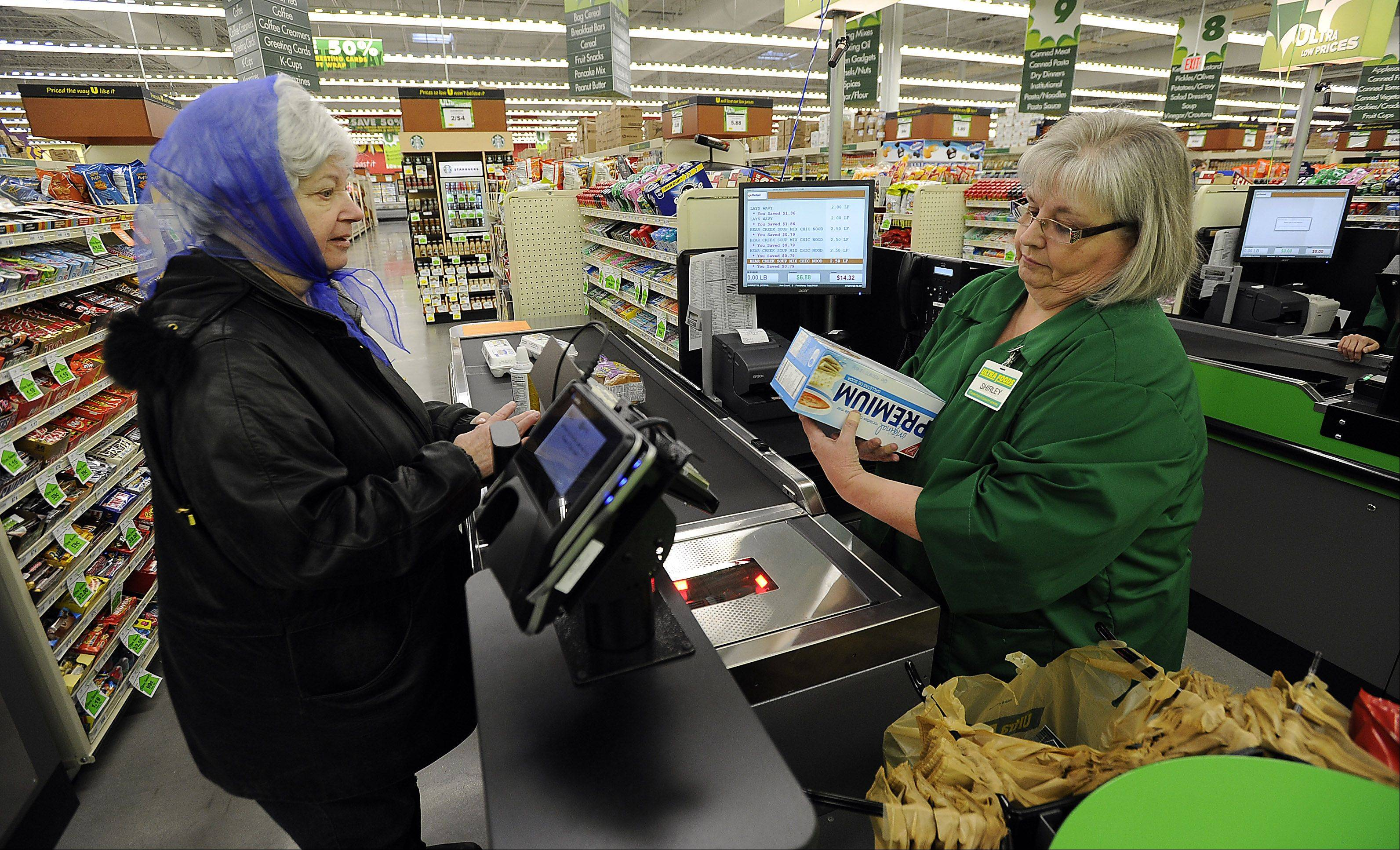 Pat Kennedy of Arlington Heights was the third customer through the checkout lane for clerk Shirley Whipple on the first day of the grand opening at Ultra Foods in Prospect Heights.