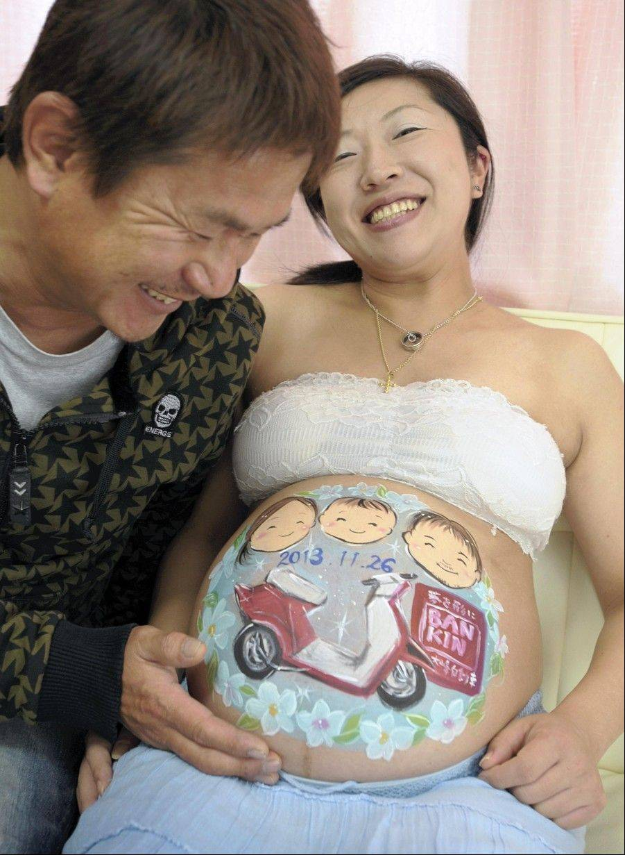 A woman and her husband smile while looking at a belly painting depicting their family.