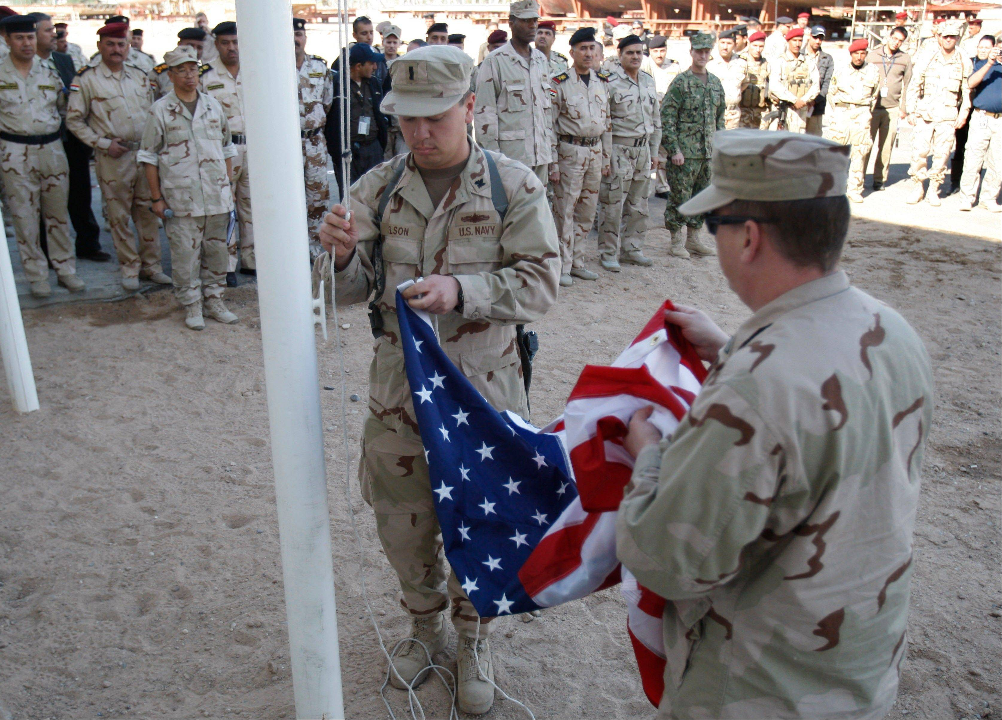 U.S. servicemen fold the American flag after it was lowered during the handover ceremony of a military base in Basra, Iraq, Dec. 1, 2011.