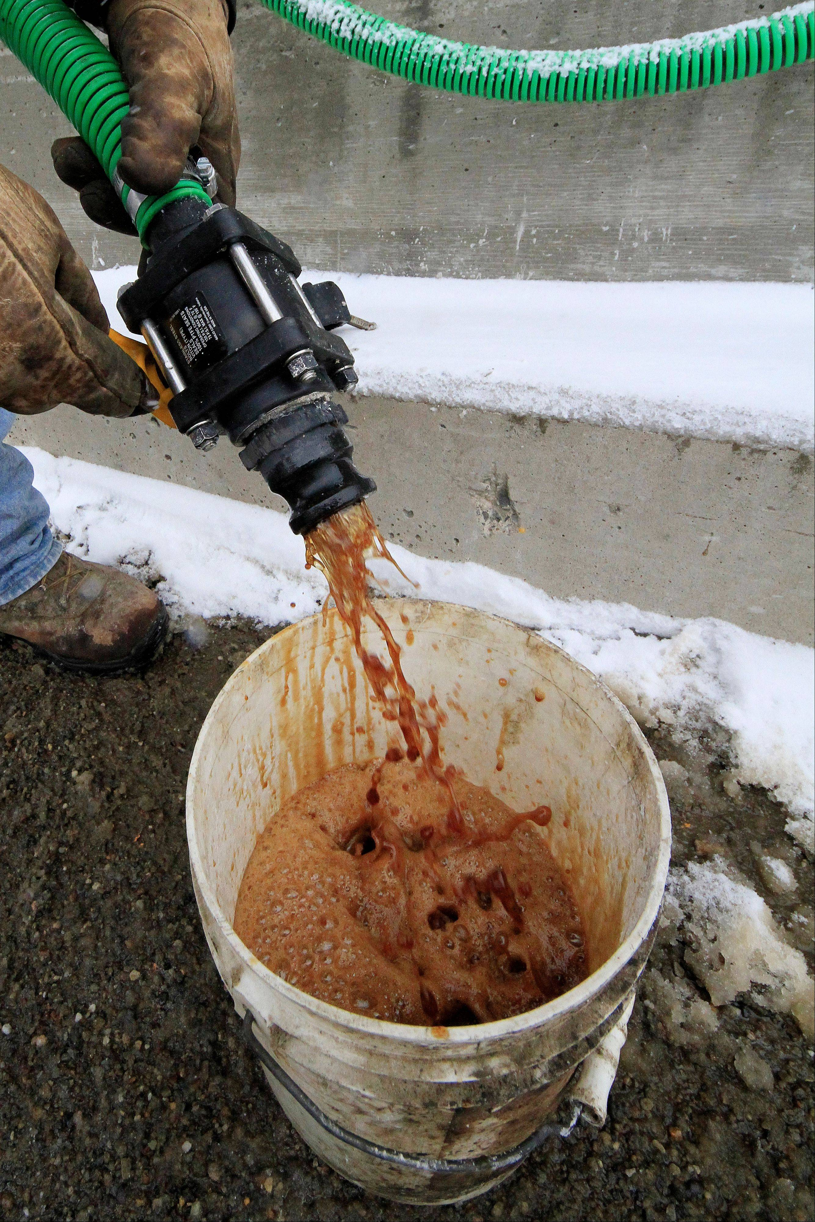 In a demonstration, a bucket is filled with beet juice at the Pennsylvania Department of Transportation's Butler, Pa., maintenance facility, Monday. Because rock salt is largely ineffective below 16 degrees, road salt is mixed with additives, such as beet juice and cheese brine, to keep it working in temperatures as low as minus 25.