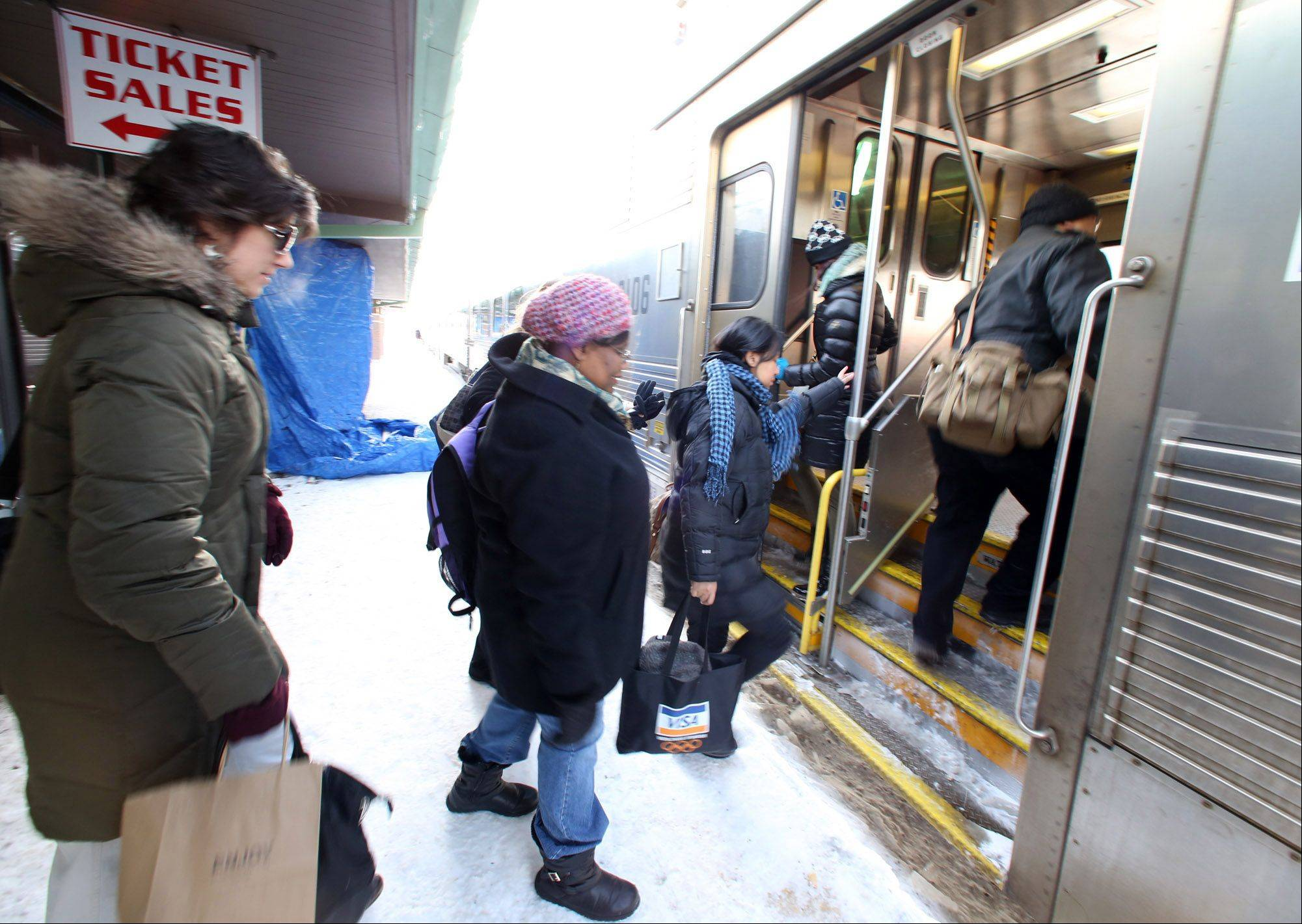 Commuters board an inbound train at the Des Plaines Metra Station on Tuesday.