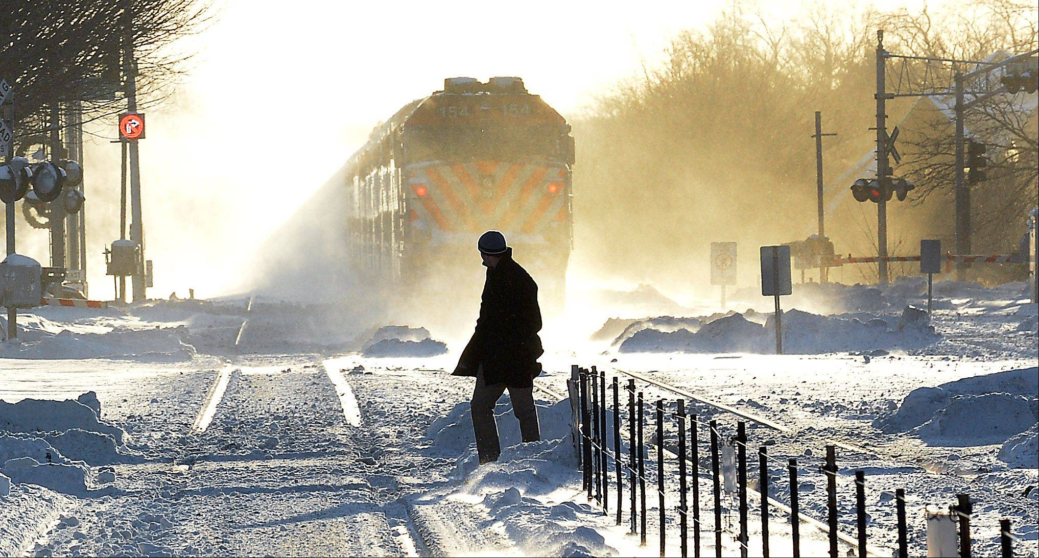 An outbound Metra gets lost in the blowing snow as man walks to the Arlington Heights train station in the subfreezing temperatures on Monday morning.