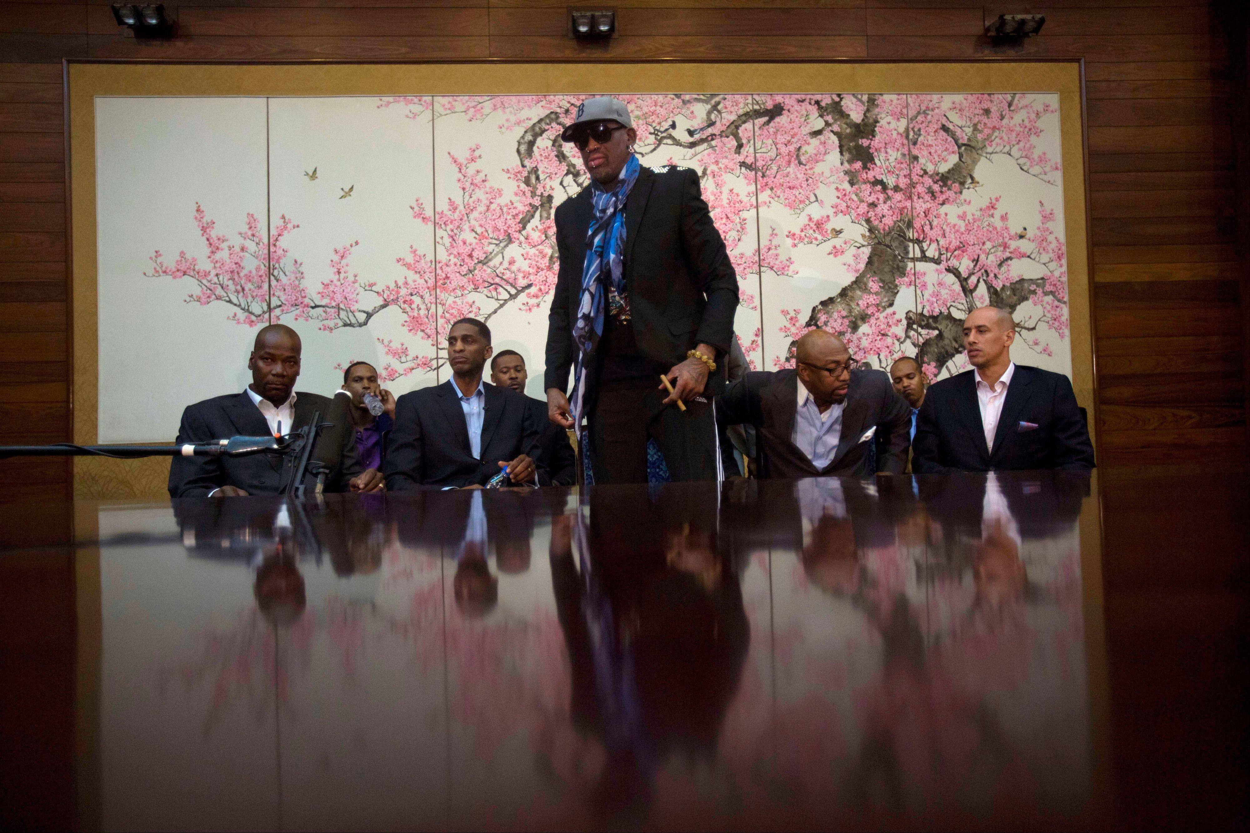 "Dennis Rodman stands up to leave after he and fellow U.S. basketball players completed a television interview at a Pyongyang, North Korea hotel Tuesday, Jan. 7, 2014. Rodman came to the North Korean capital with a team of USA basketball stars for an exhibition game on Jan. 8, the birthday of North Korean leader Kim Jong Un. From left to right are Cliff Robinson, Jerry Dupree, Charles D. Smith, unidentified, Vin Baker, Andre ""Silk"" Poole and Doug Christie."