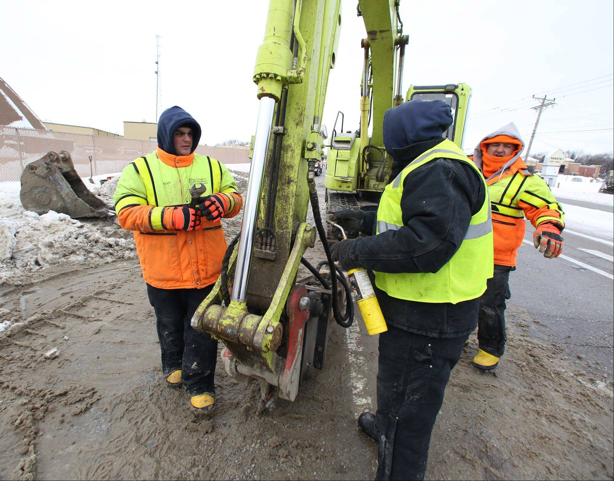 Schaumburg Public Works employees try to unfreeze equipment while digging to expose a water main break at Algonquin and Meacham Roads on Tuesday in Schaumburg.
