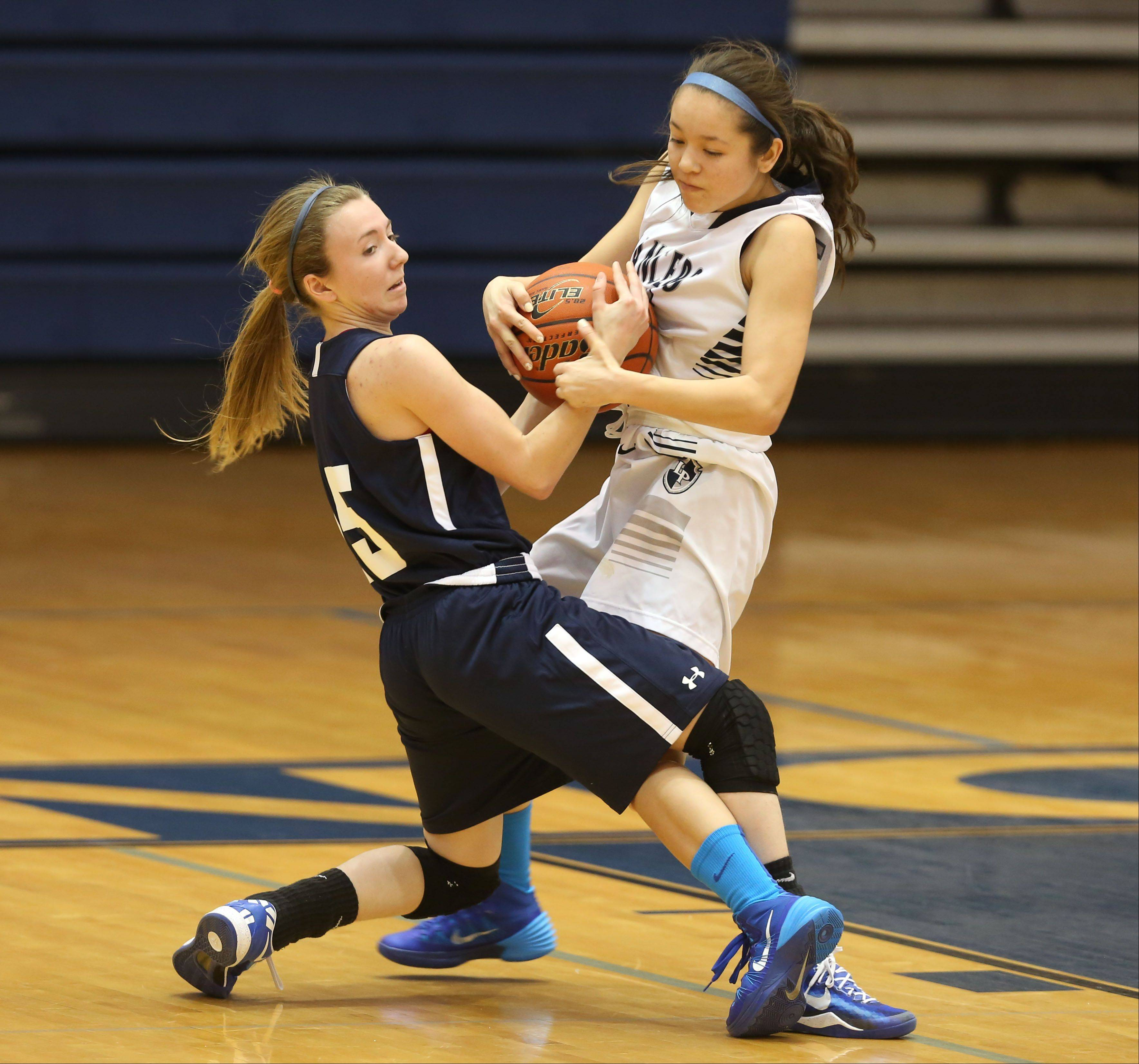 Addison Trail's Connie Barkoulies, left, fights for ball control with Lake Park's Kelly Adams during Friday's basketball game in Roselle.