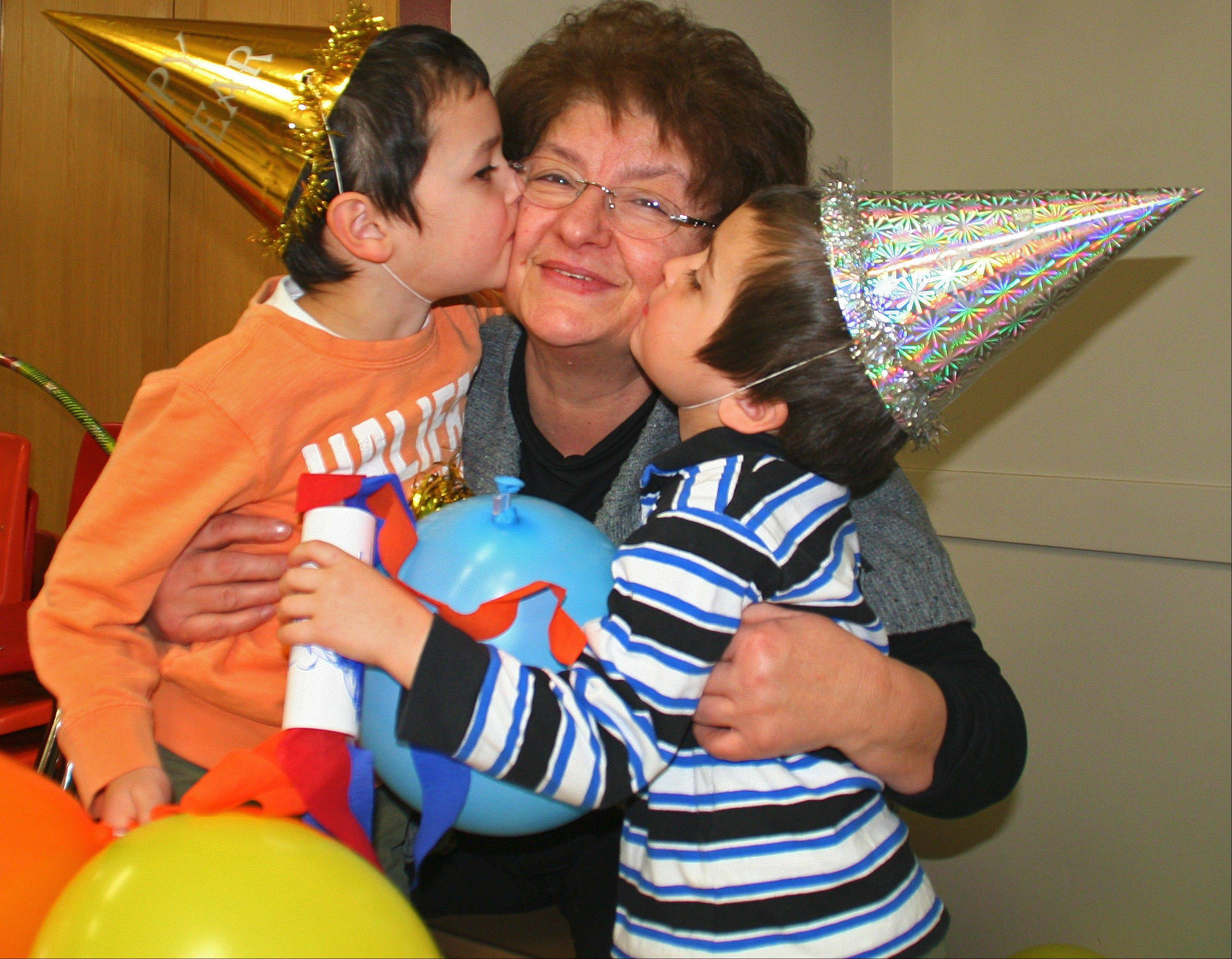 Muharem Sarancic, left, 5, and his brother, Kerim, 3, kiss their grandmother Azra at the stroke of 12 at the Preschool Noon Year's Eve party on Dec. 31, at Prairie Lakes Community Center.