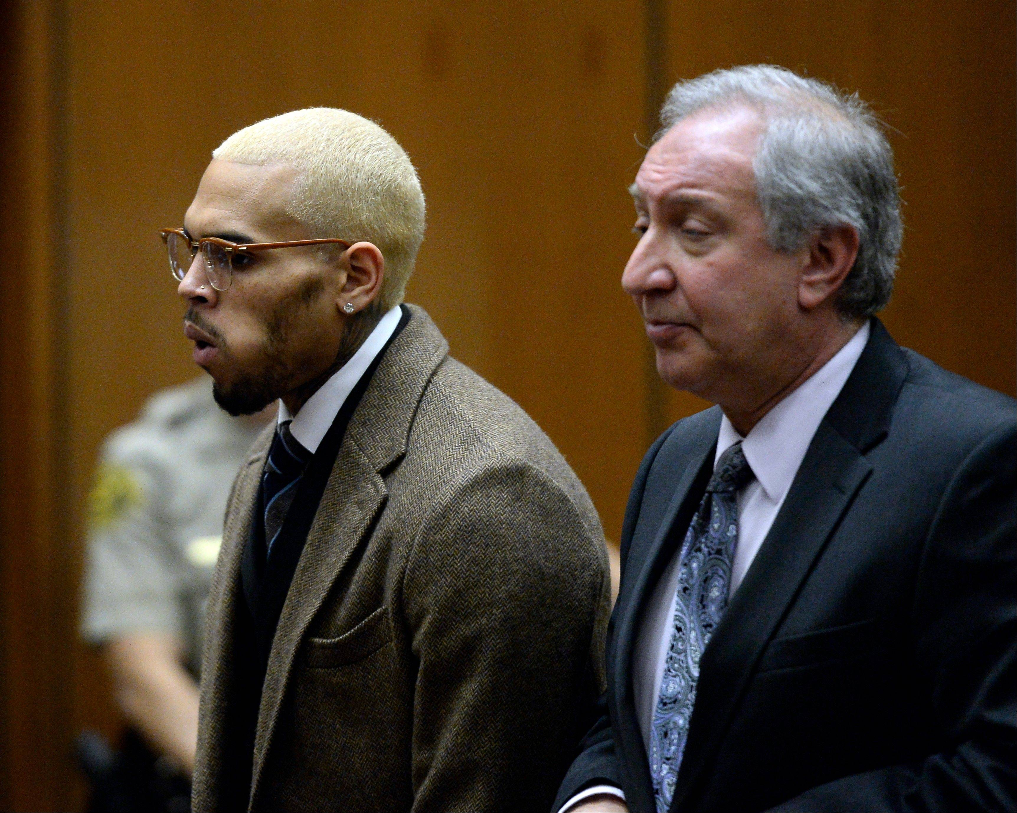 Singer Chris Brown, left, appears in court in December 2013 with his attorney Mark Geragos, in Los Angeles. Brown is expected to return to court for a status hearing in a case in which he's accused of hitting a man outside a Washington, D.C., hotel. The R&B singer was arrested in October after a man said the singer hit him outside the W Hotel. Brown and his bodyguard each face a misdemeanor assault charge.