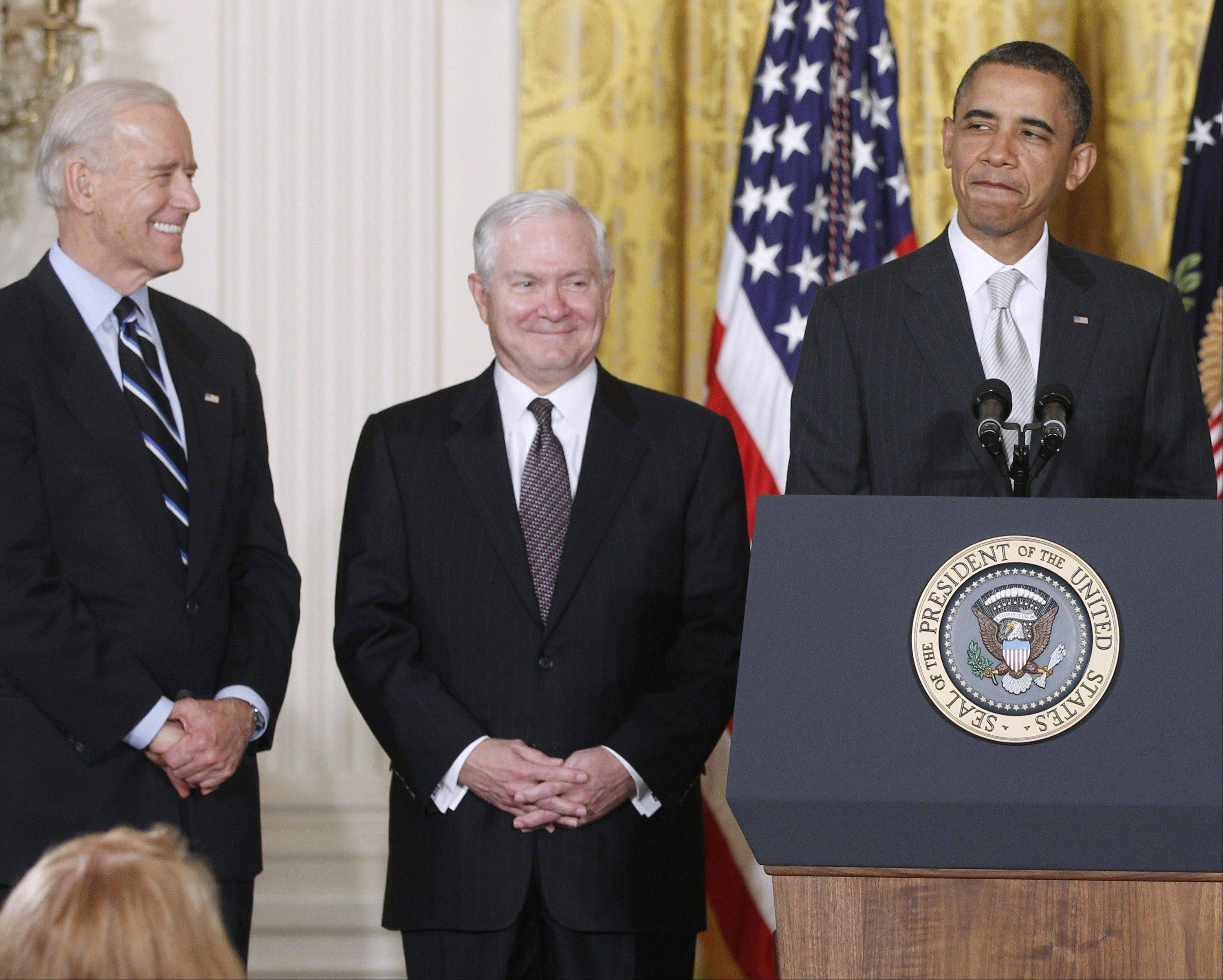 President Barack Obama stands in the East Room of the White House in Washington with, from left: Vice President Joe Biden and outgoing Defense Secretary Robert Gates. The White House is bristling over former Defense Secretary Robert Gates� new memoir accusing President Barack Obama of showing too little enthusiasm for the U.S. war mission in Afghanistan and sharply criticizing Vice President Joe Biden�s foreign policy instincts.