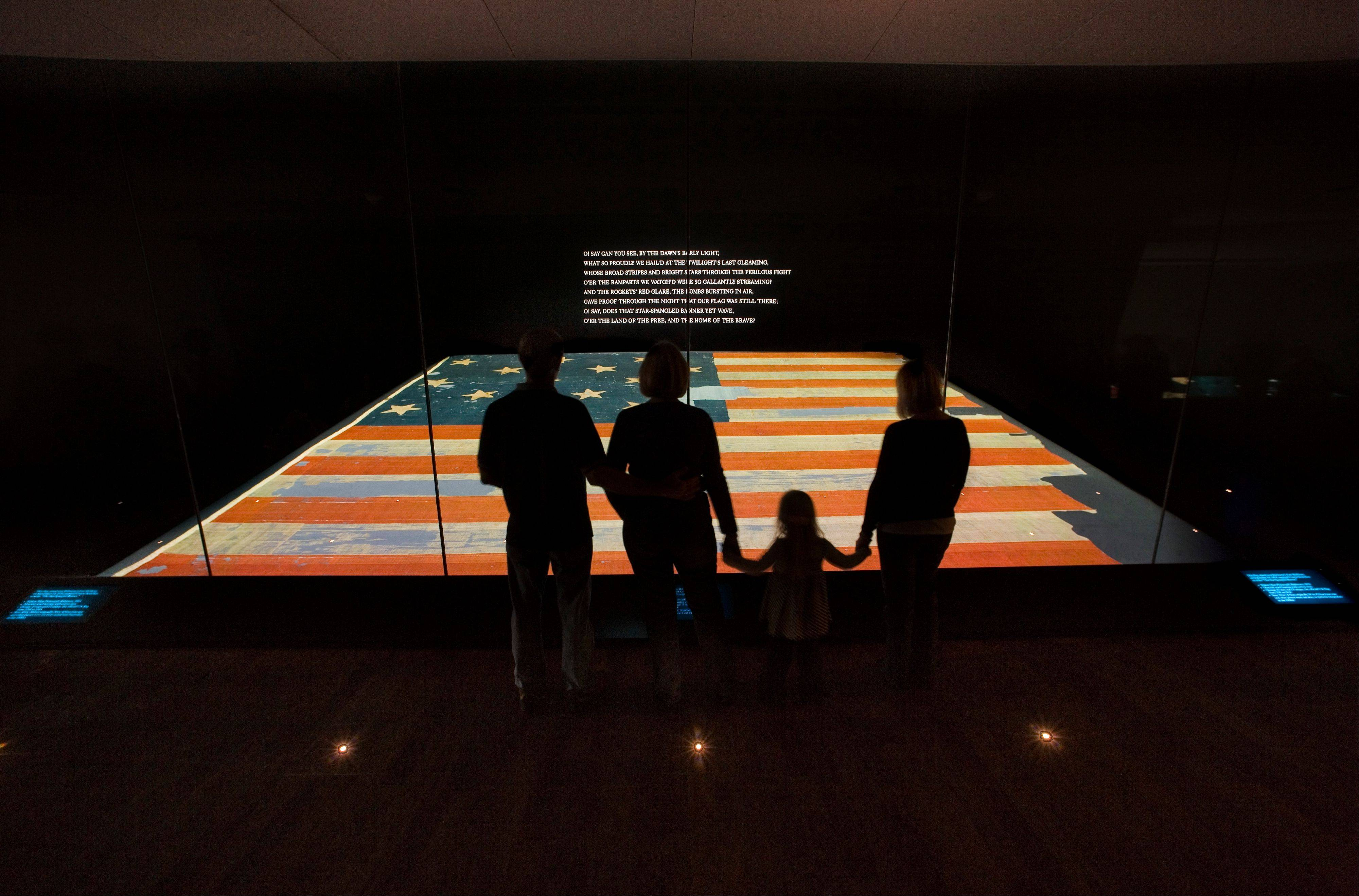 This handout photo provided by the Smithsonian Institution, taken in Nov. 2008, shows a family viewing the Star Spangled Banner at the Smithsonian's National Museum of American History in Washington.