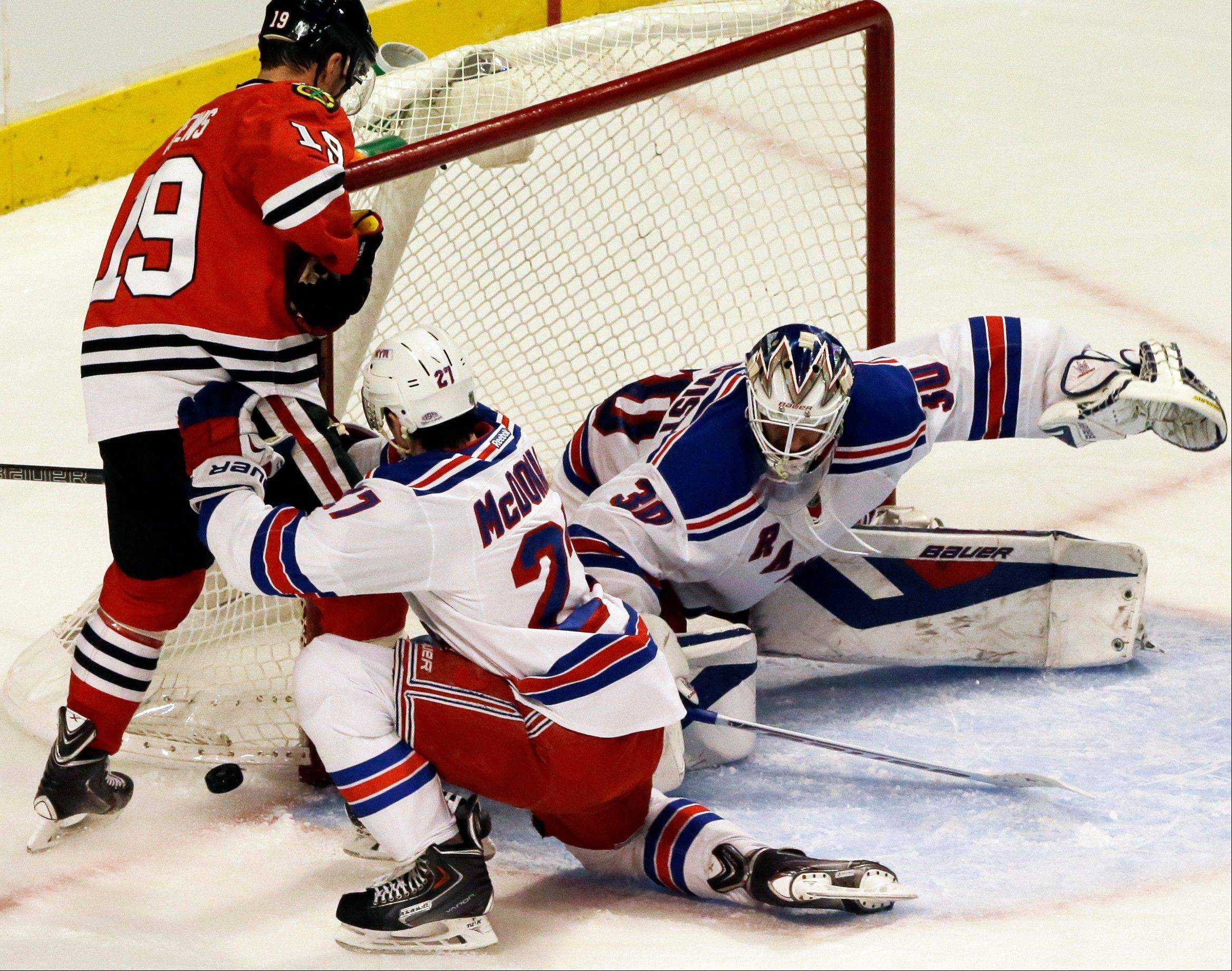 Rangers goalie Henrik Lundqvist blocks a shot by the Blackhawks� Jonathan Toews as New York�s Ryan McDonagh helps his goalie.