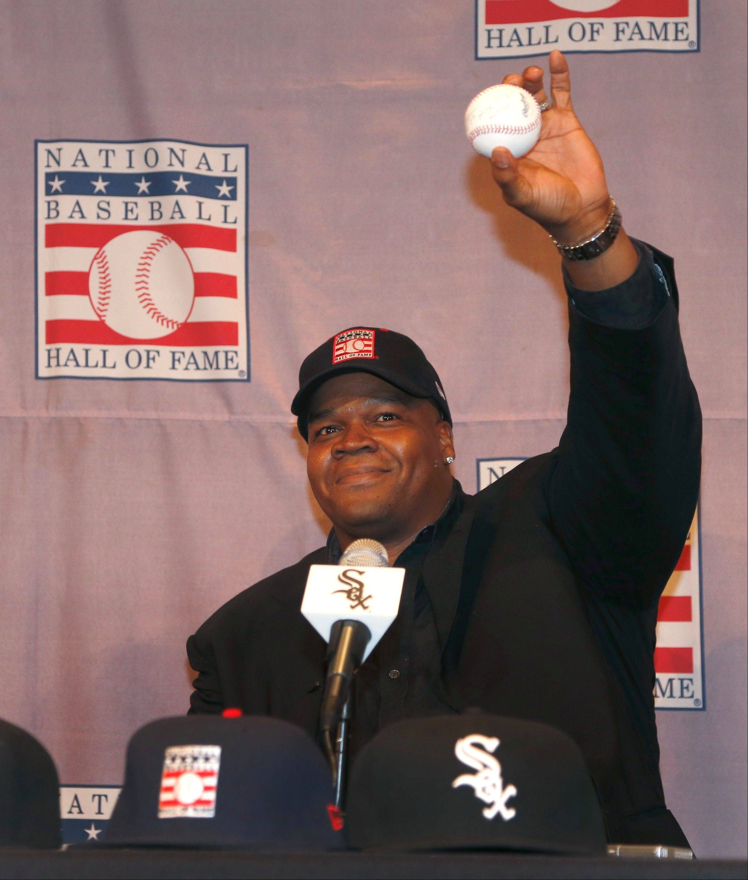 "Frank Thomas holds up a baseball he signed ""Frank Thomas HOF"" during a news conference Wednesday to discuss the announcement of his selection as a first-ballot Hall of Famer."
