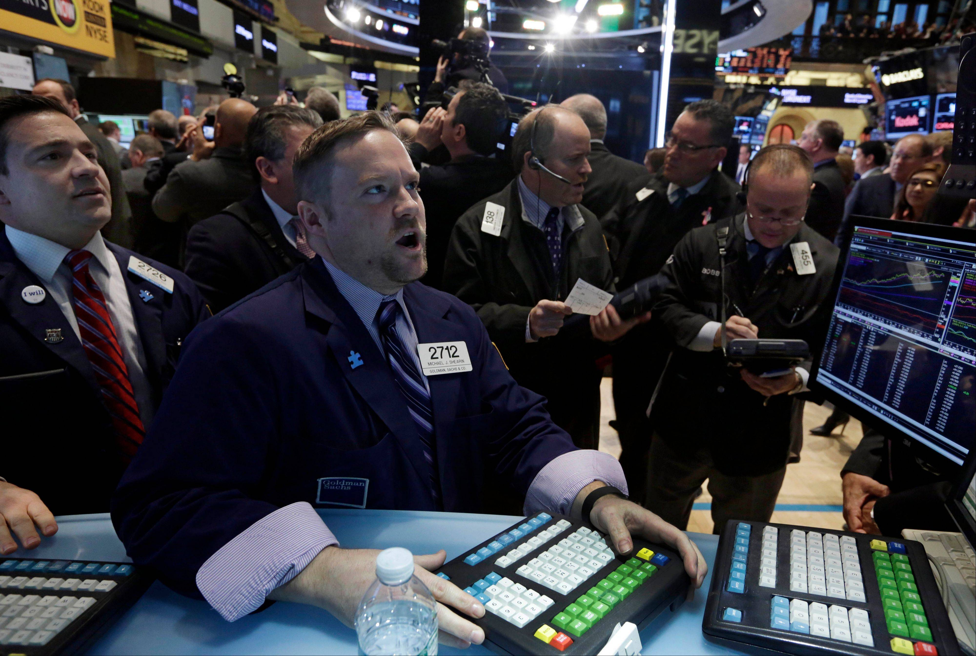 Specialist Michael Shearin, foreground center, works at his post on the floor of the New York Stock Exchange Wednesday.